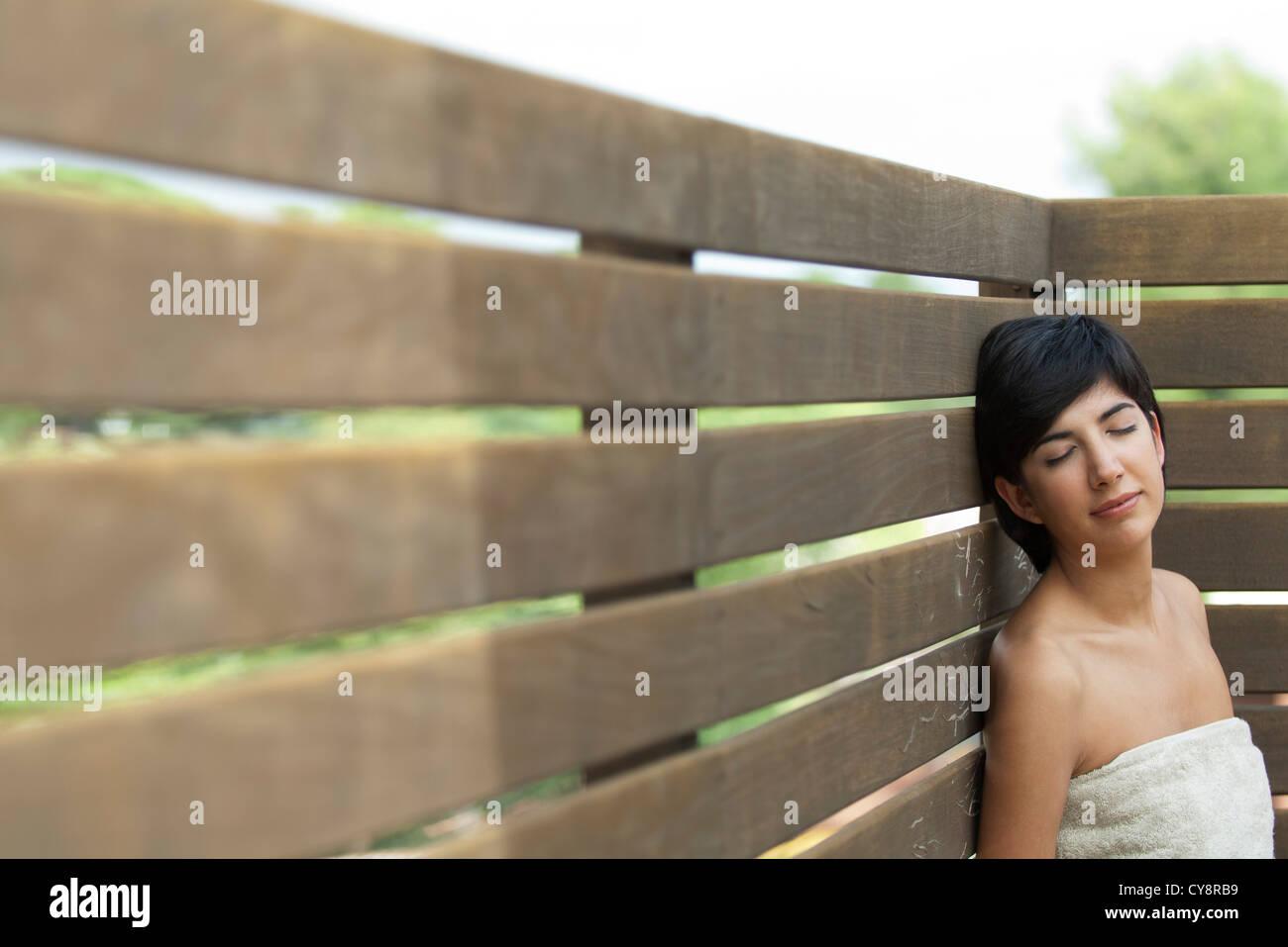 Mujer joven envuelta en una toalla relajante al aire libre con los ojos cerrados Imagen De Stock