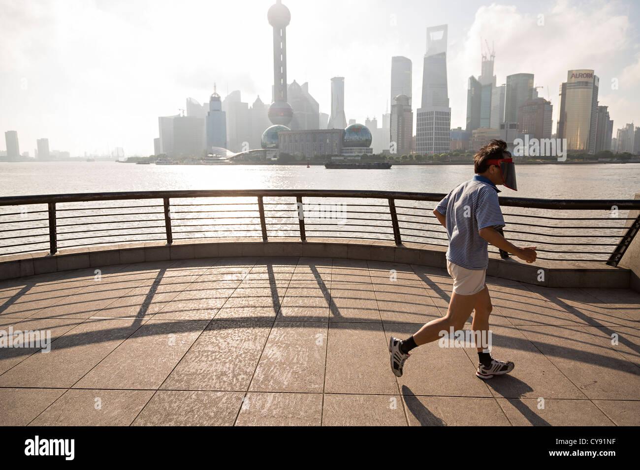 Un hombre avanza por la mañana temprano en el Bund contra el horizonte de la moderna Shangai, China Foto de stock