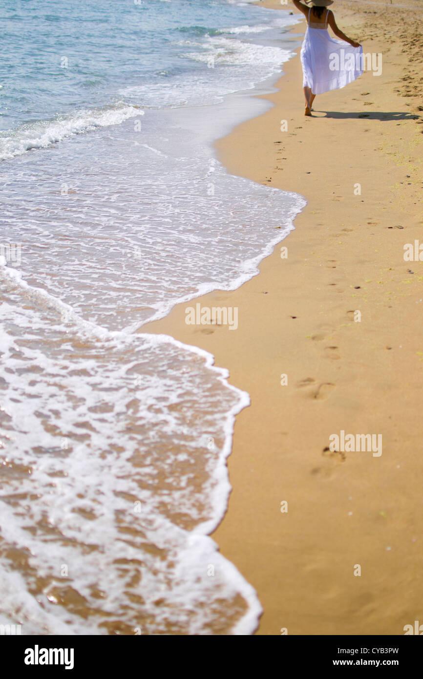 Mujer joven caminando en la playa de arena vistiendo vestido