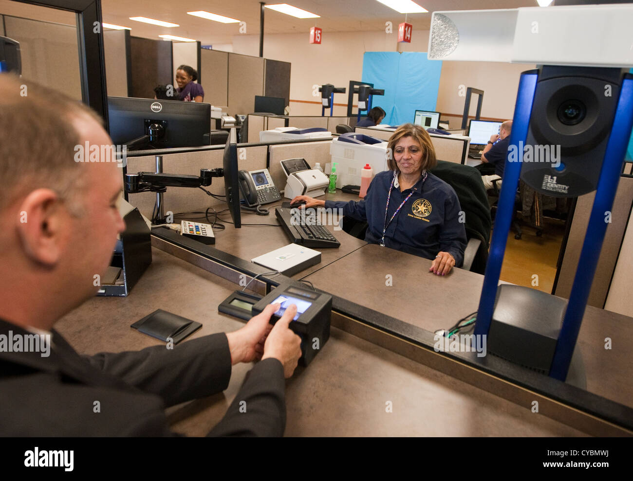 Cliente para renovar la licencia de conductor obtiene dedo-impresos y completa el examen ocular en el Departamento Imagen De Stock
