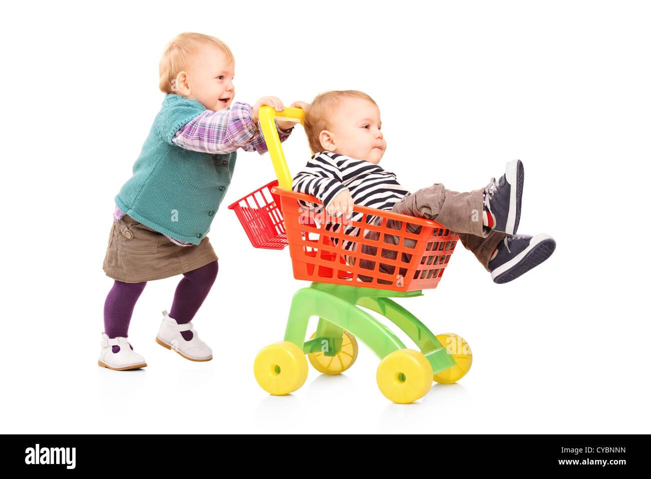 Nino Nina Empujar A Su Hermano Gemelo En Un Carro De Juguete Aislado