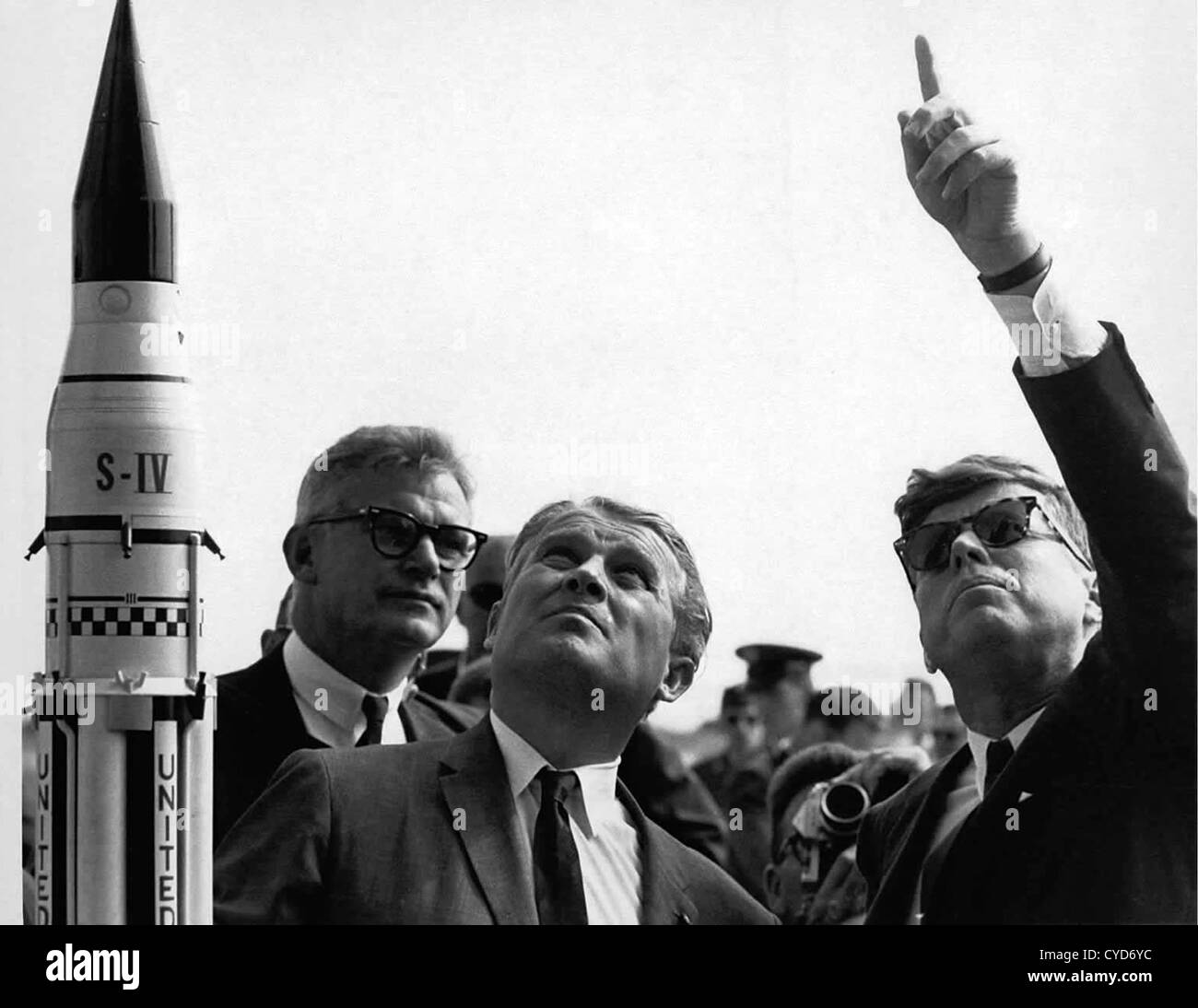 El Presidente John F. Kennedy, a la derecha, obtiene una explicación del sistema de lanzamiento Saturno V desde Foto de stock