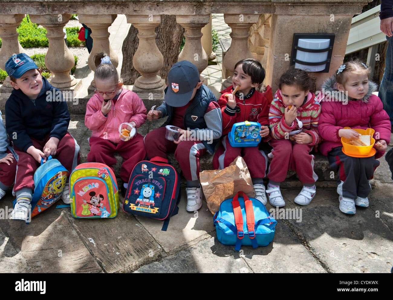 Malta. Los niños pequeños comer sus comidas empaquetadas durante una excursión escolar al Presidente's Imagen De Stock
