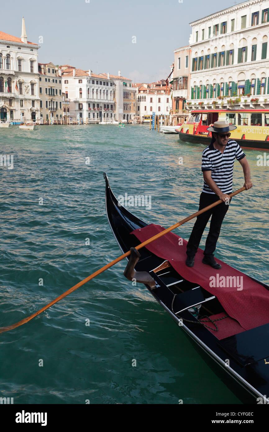 Gondolero en el Gran Canal de Venecia vistiendo la camiseta pelado  tradicional y sombrero de paja c8d2e7f41e7