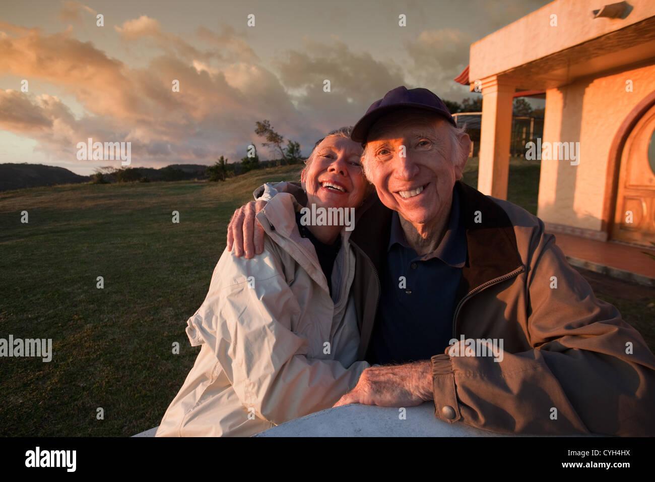 Amorosa pareja de ancianos sonriendo a la mesa en las montañas Imagen De Stock