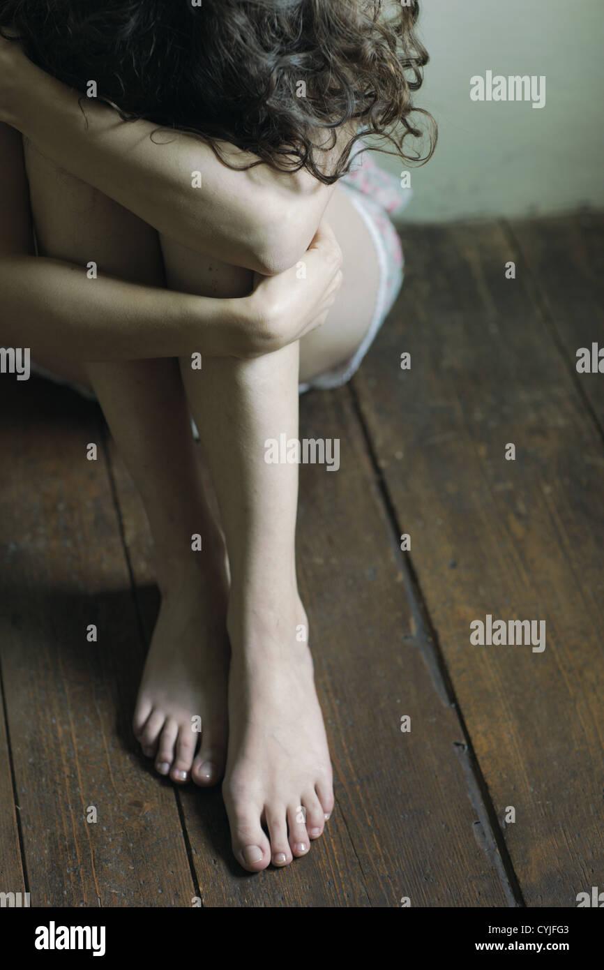 Triste mujer sentada sola en una habitación vacía Imagen De Stock