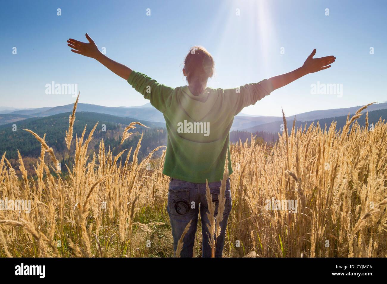 Niña feliz, disfrutando de la belleza del soleado día de otoño en lo alto de las montañas Imagen De Stock