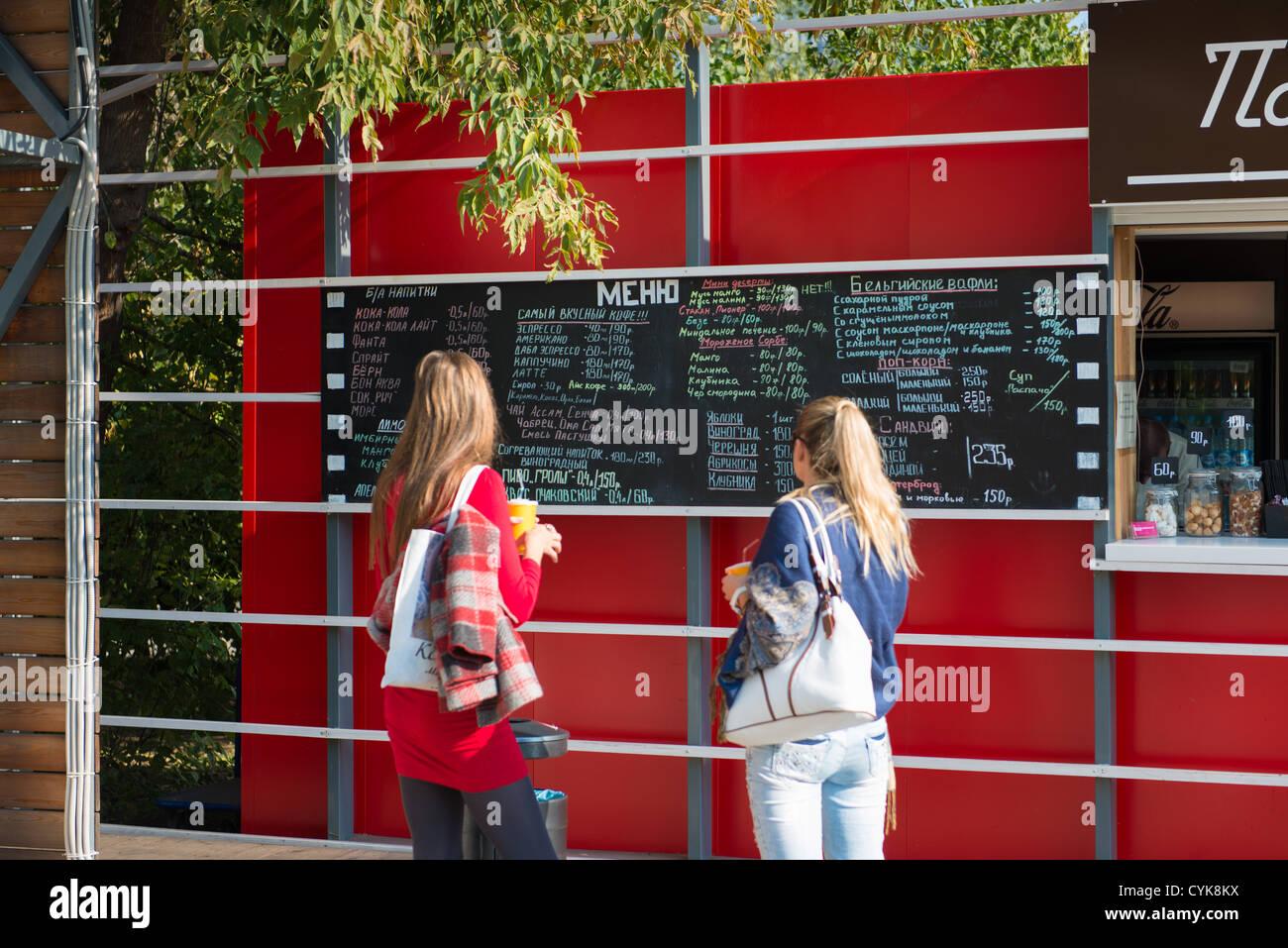 Las niñas leer pizarra menú en el parque Gorky, Moscú Imagen De Stock