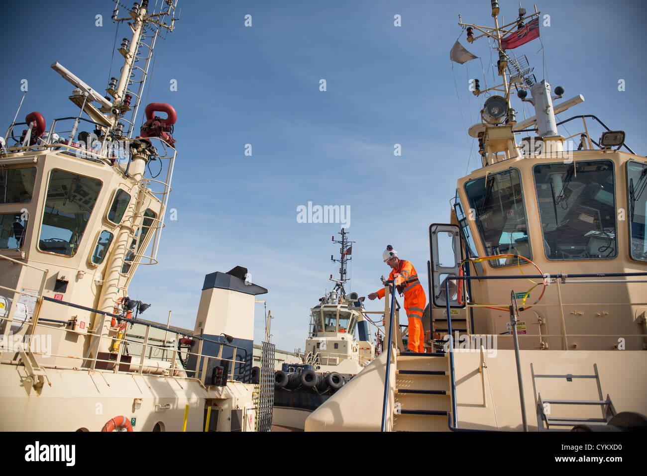 Trabajador de pie en la cubierta del barco de remolque Foto de stock