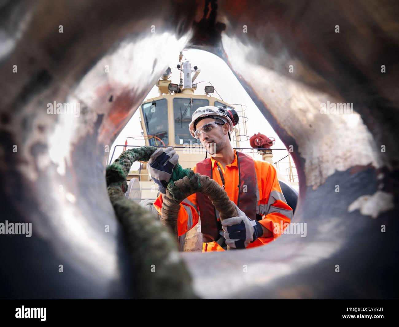 Trabajador de remolcadores tirando de la cuerda en la cubierta Foto de stock