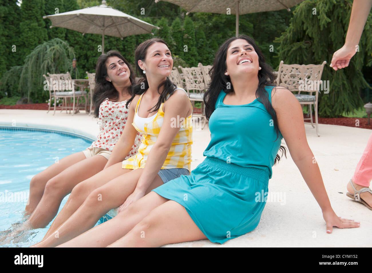 Las mujeres los pies colgando en la piscina Foto de stock