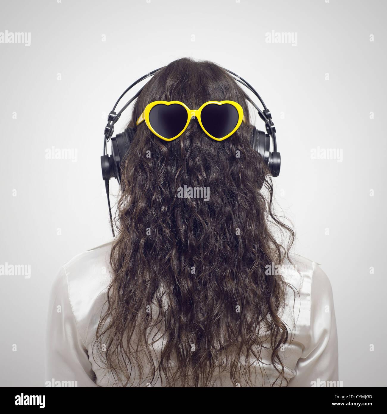 Mujer joven escuchando música, vista posterior Imagen De Stock