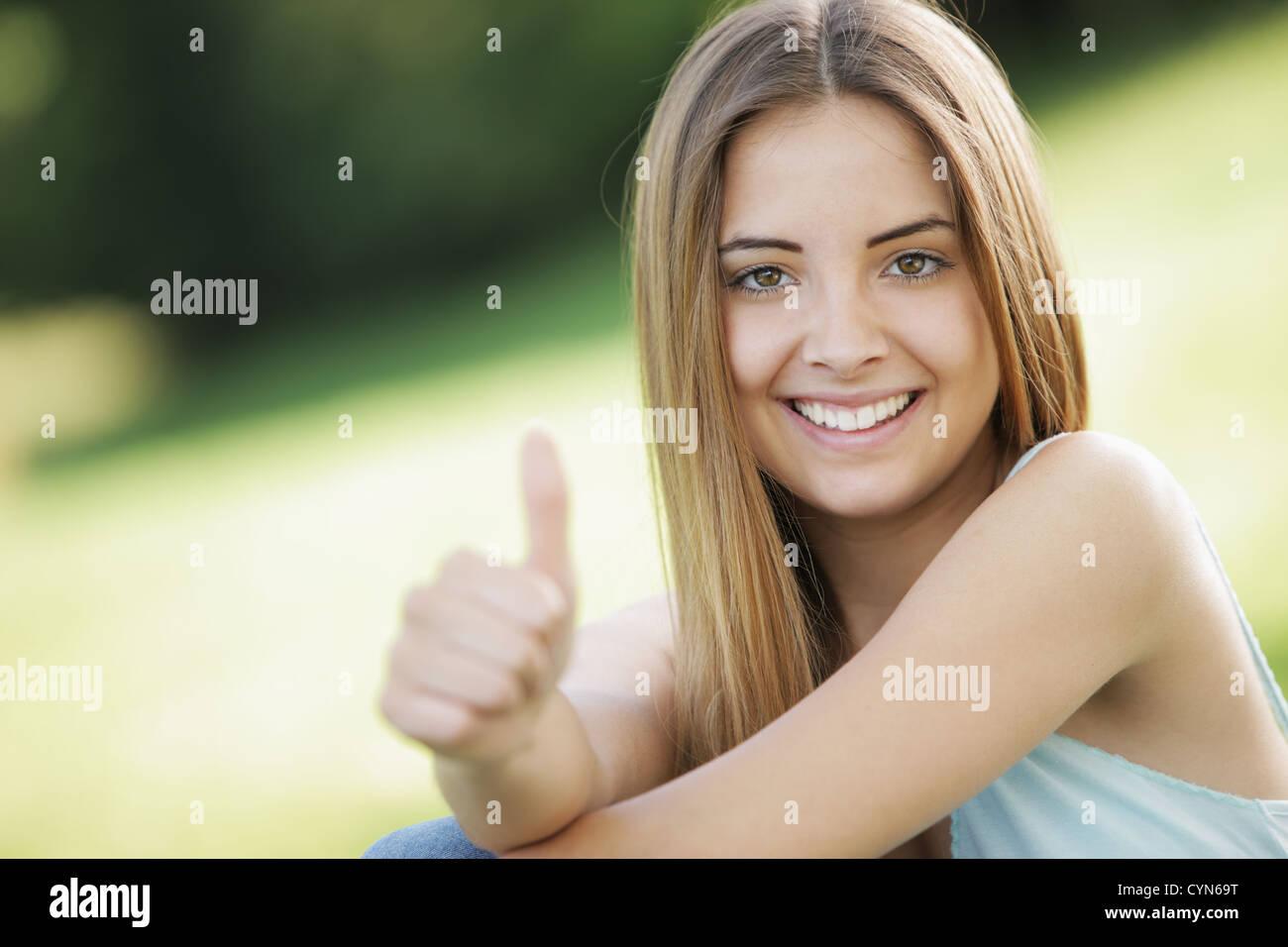 Hermosa joven mostrando pulgar arriba firmar Imagen De Stock