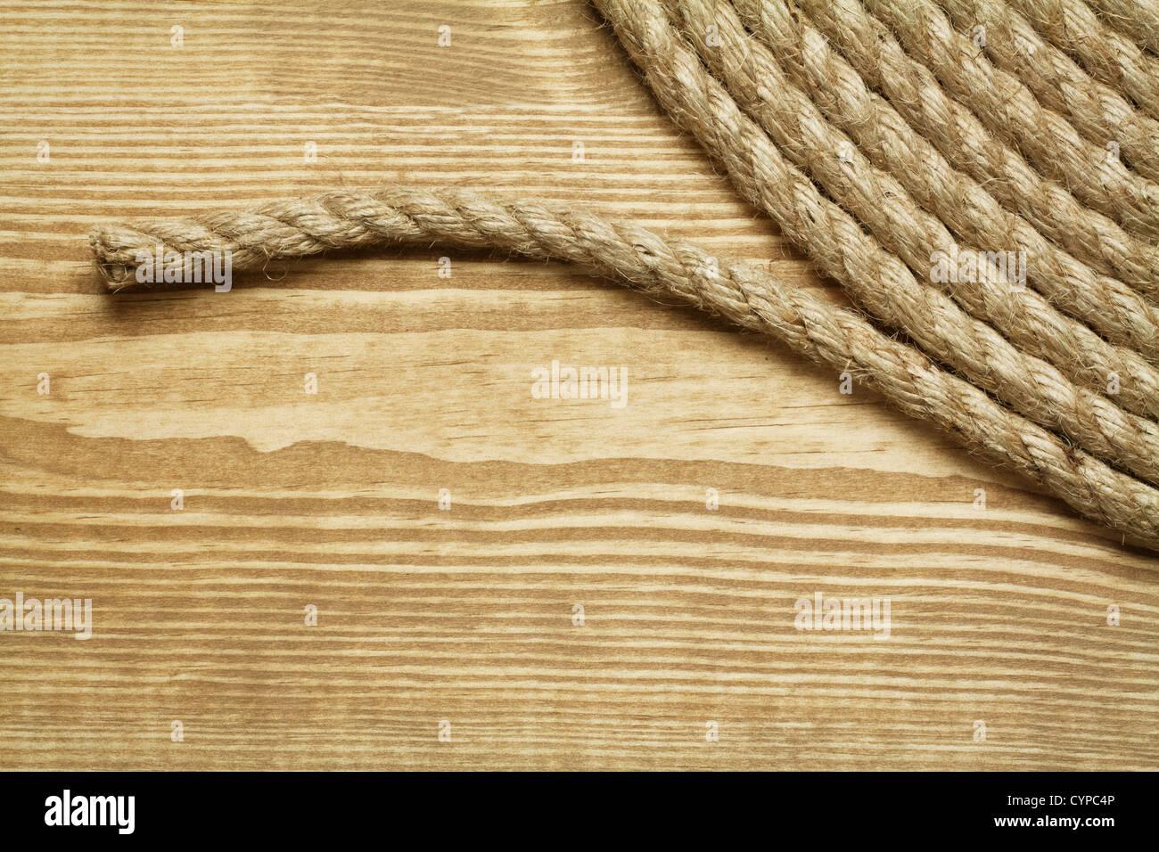 Rollo de cuerda áspera sobre fondo de madera Imagen De Stock