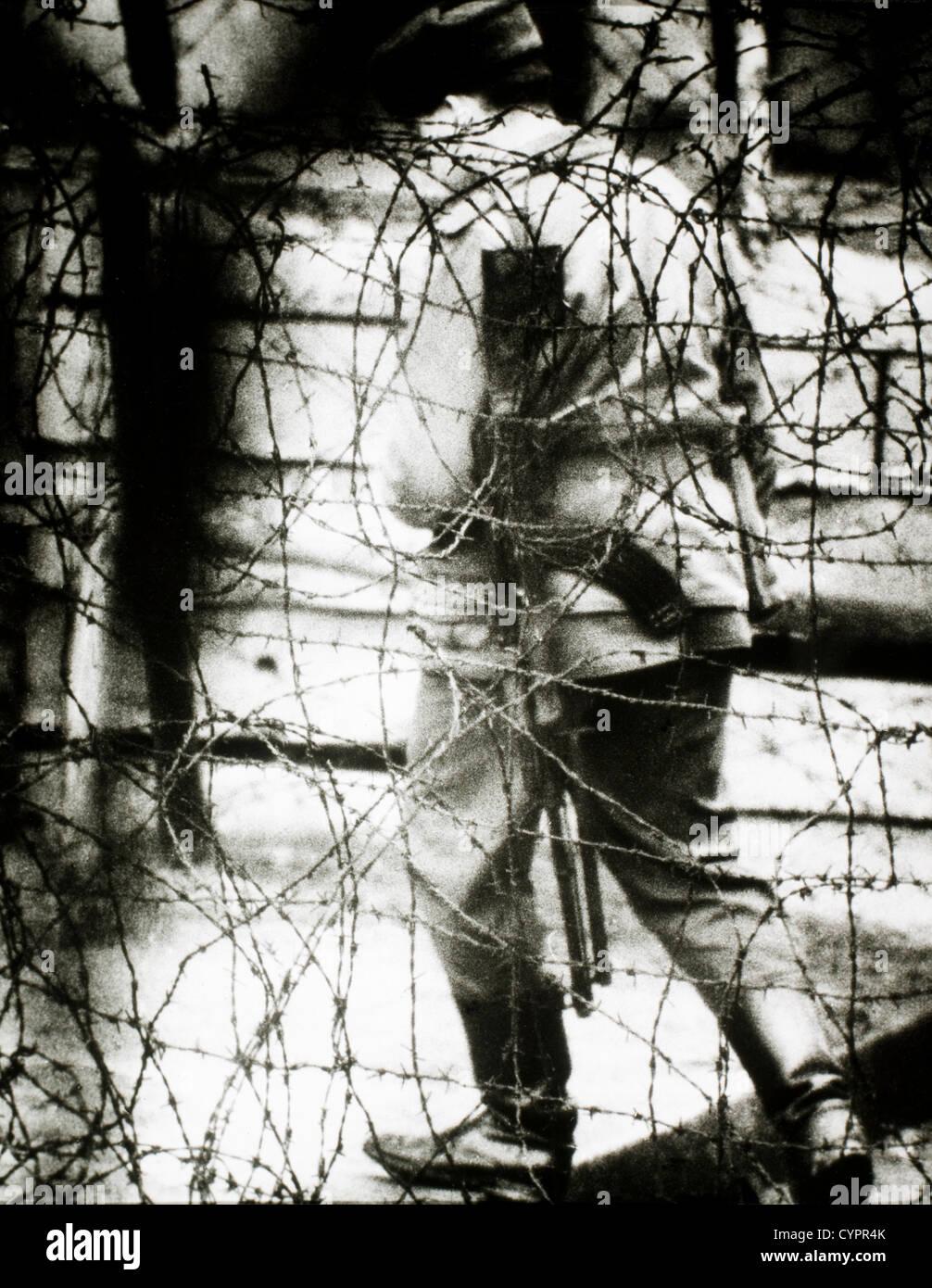 La Guardia Fronteriza de Alemania oriental vistos a través de la valla de alambre de espino, 1965 Imagen De Stock