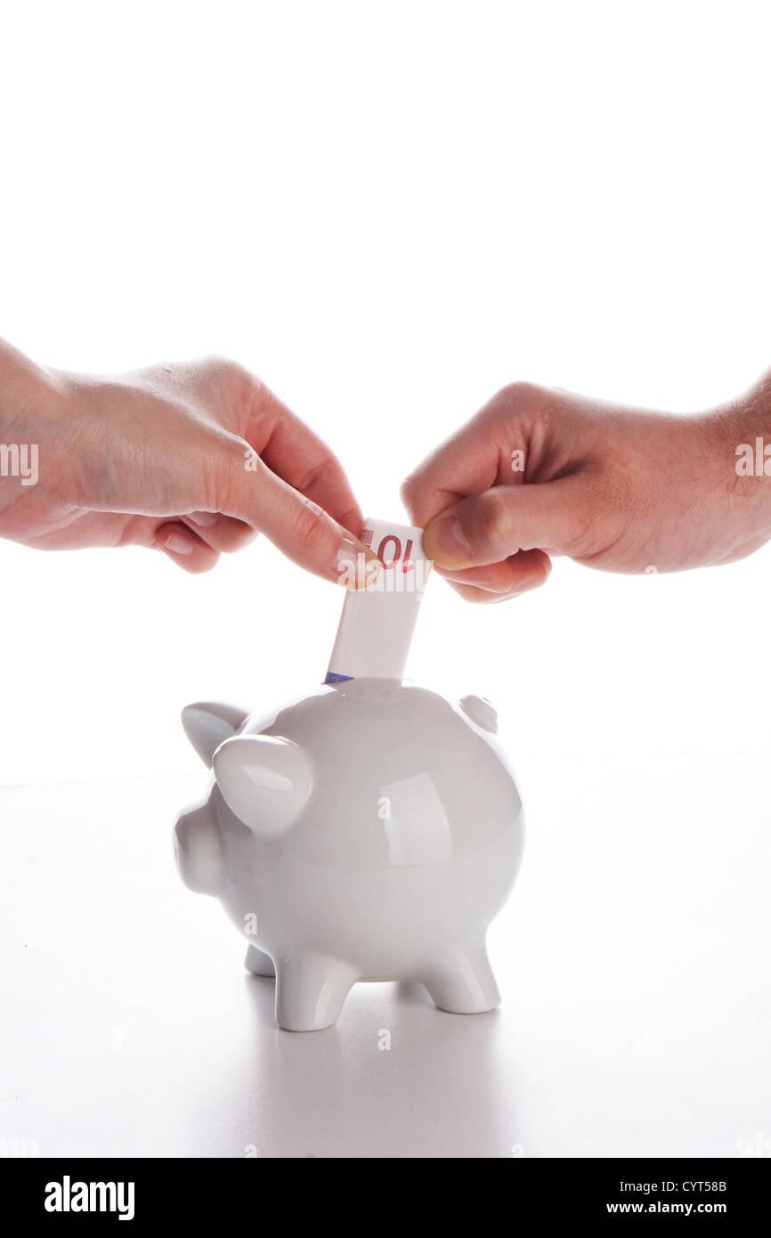 Hucha, pareja, manos y divisa euro sobre blanco Imagen De Stock