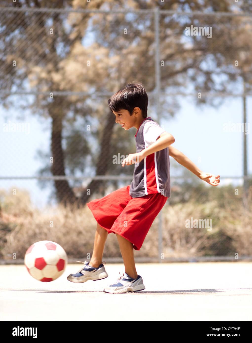 Chico en acción disfrutando de fútbol al aire libre Imagen De Stock