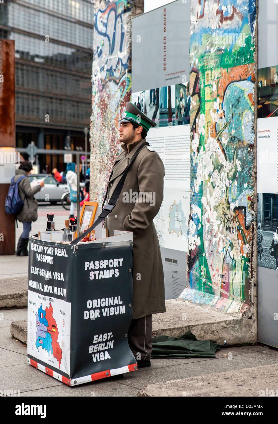 Un entrepeneur vestido con uniforme del ejército de Berlín Oriental vende sellos de visado para los pasaportes Imagen De Stock