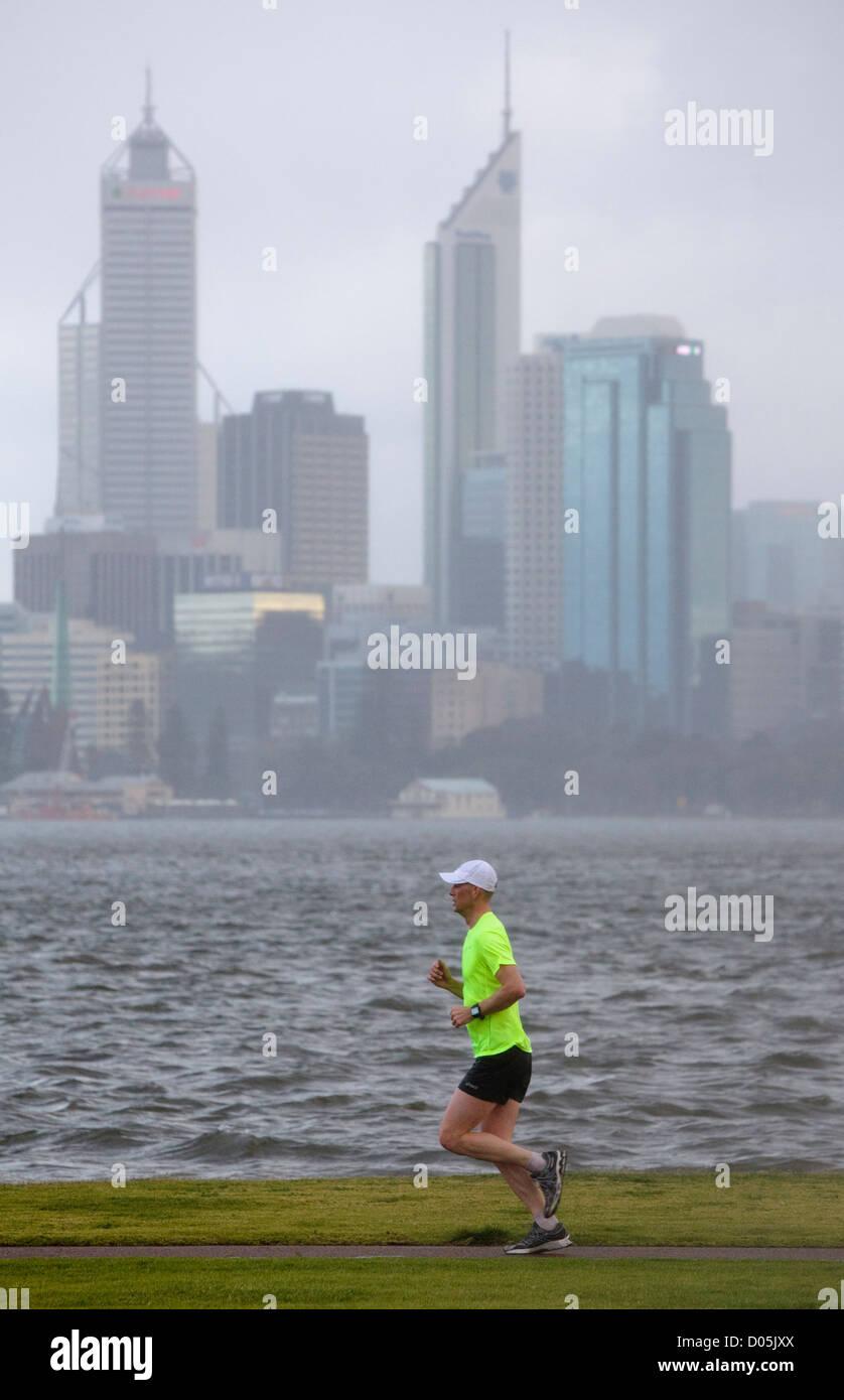 Un hombre corriendo en la lluvia con un río y la ciudad en el fondo. Foto de stock