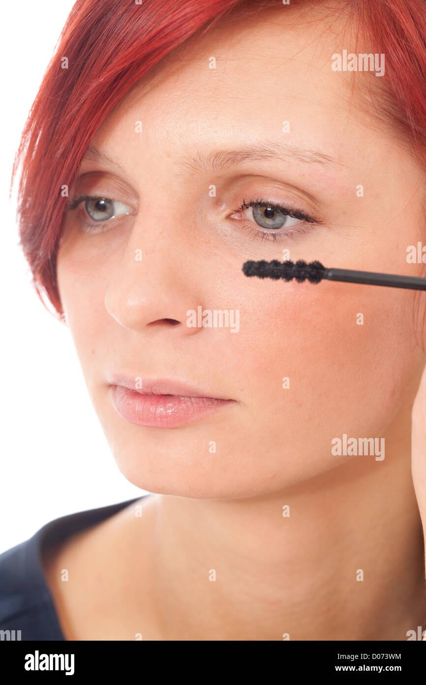 Las mujeres aplicando mascara negra en las pestañas Imagen De Stock