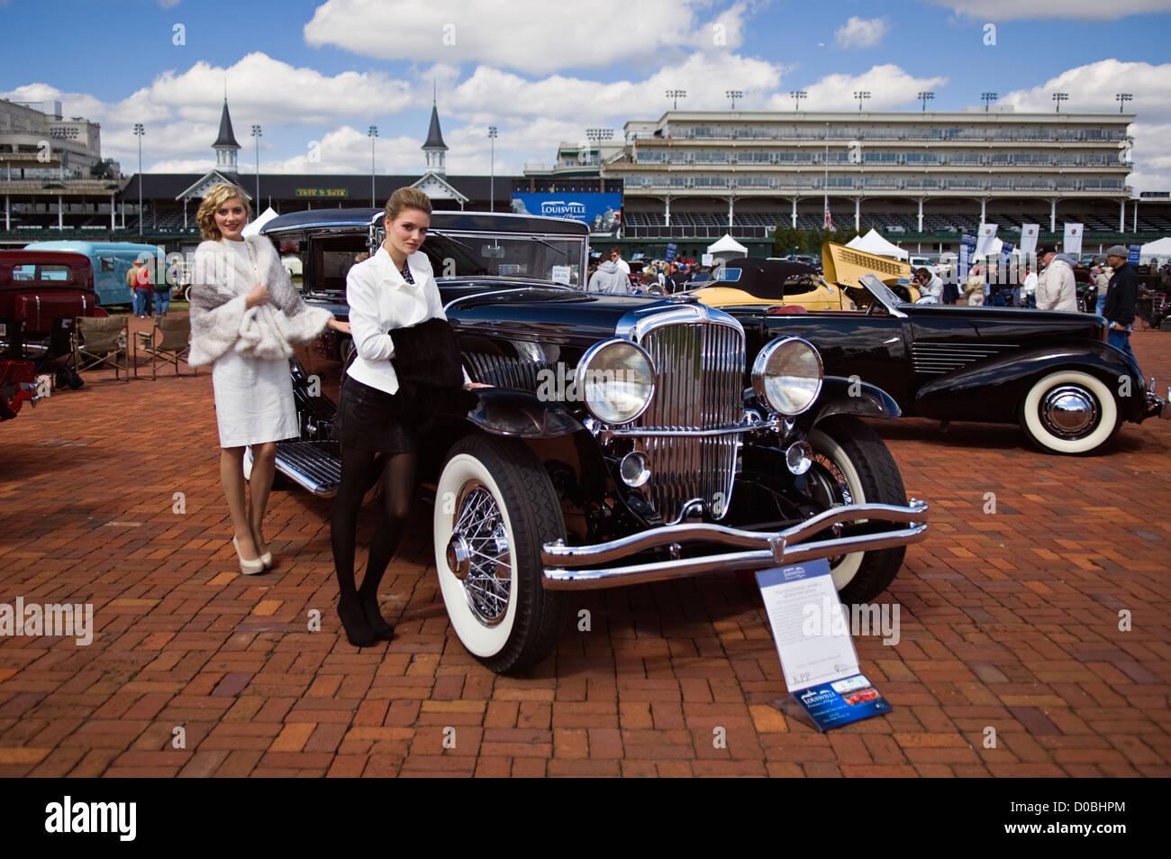 Modelos en período ropa posando junto a 1934 Duesenberg modelo J de Arlington Sedán en el Concours d'Elegance Imagen De Stock