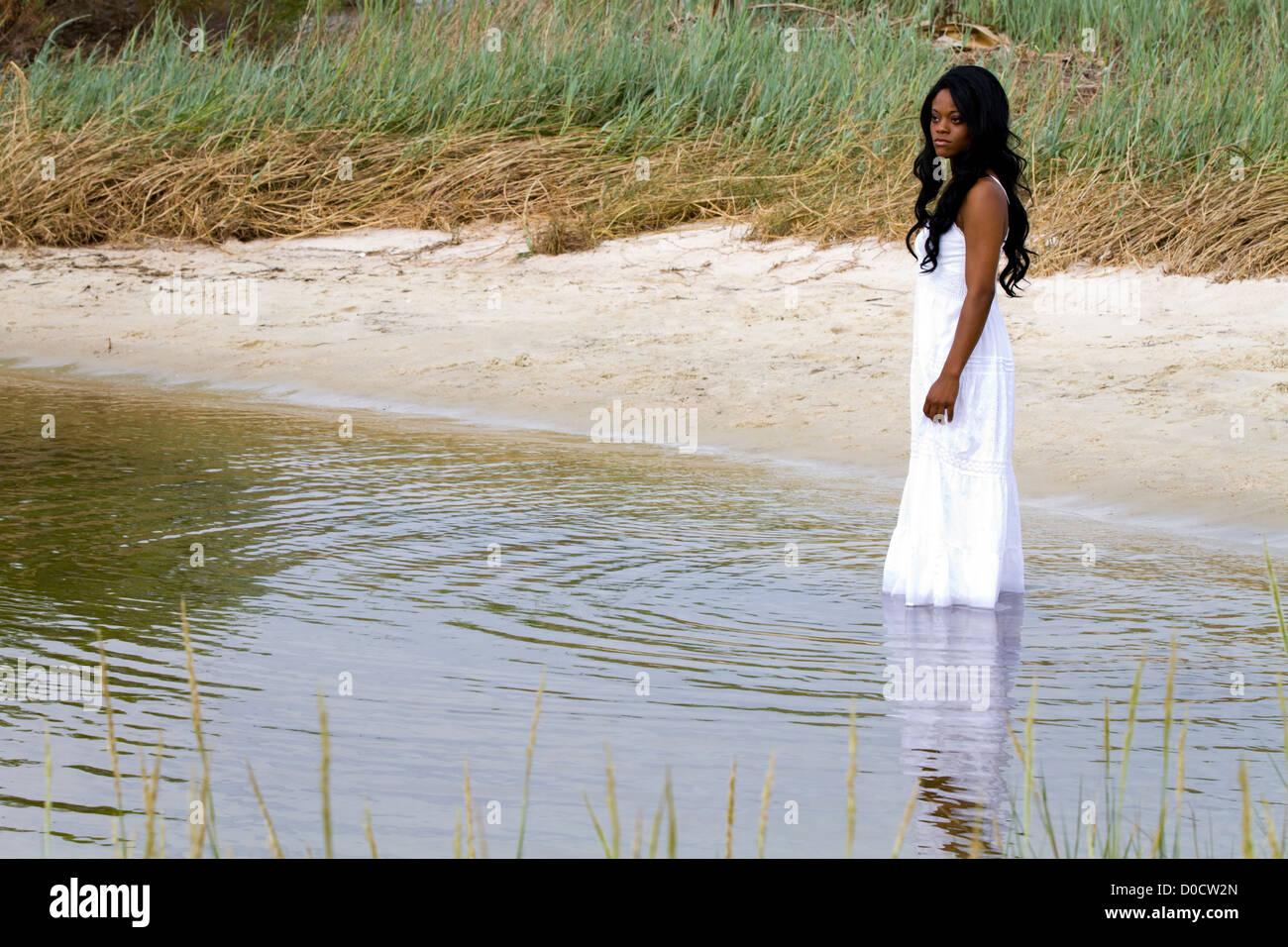 Lonely Afroamericana está abatido en aguas poco profundas con una triste mirada en su rostro pensativo. Imagen De Stock