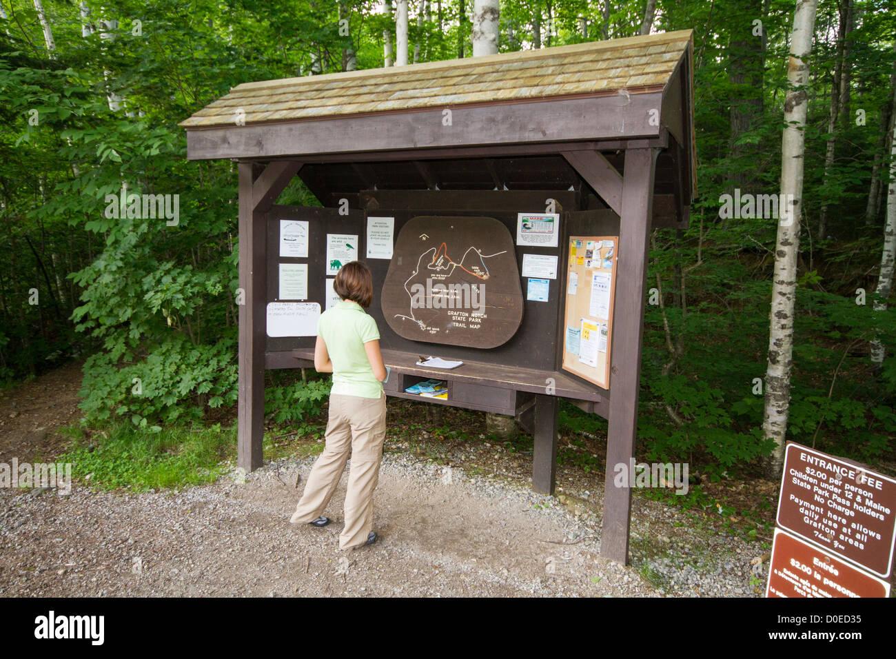 Mujer joven excursionista leer mapa/directrices al comienzo de un camino Imagen De Stock