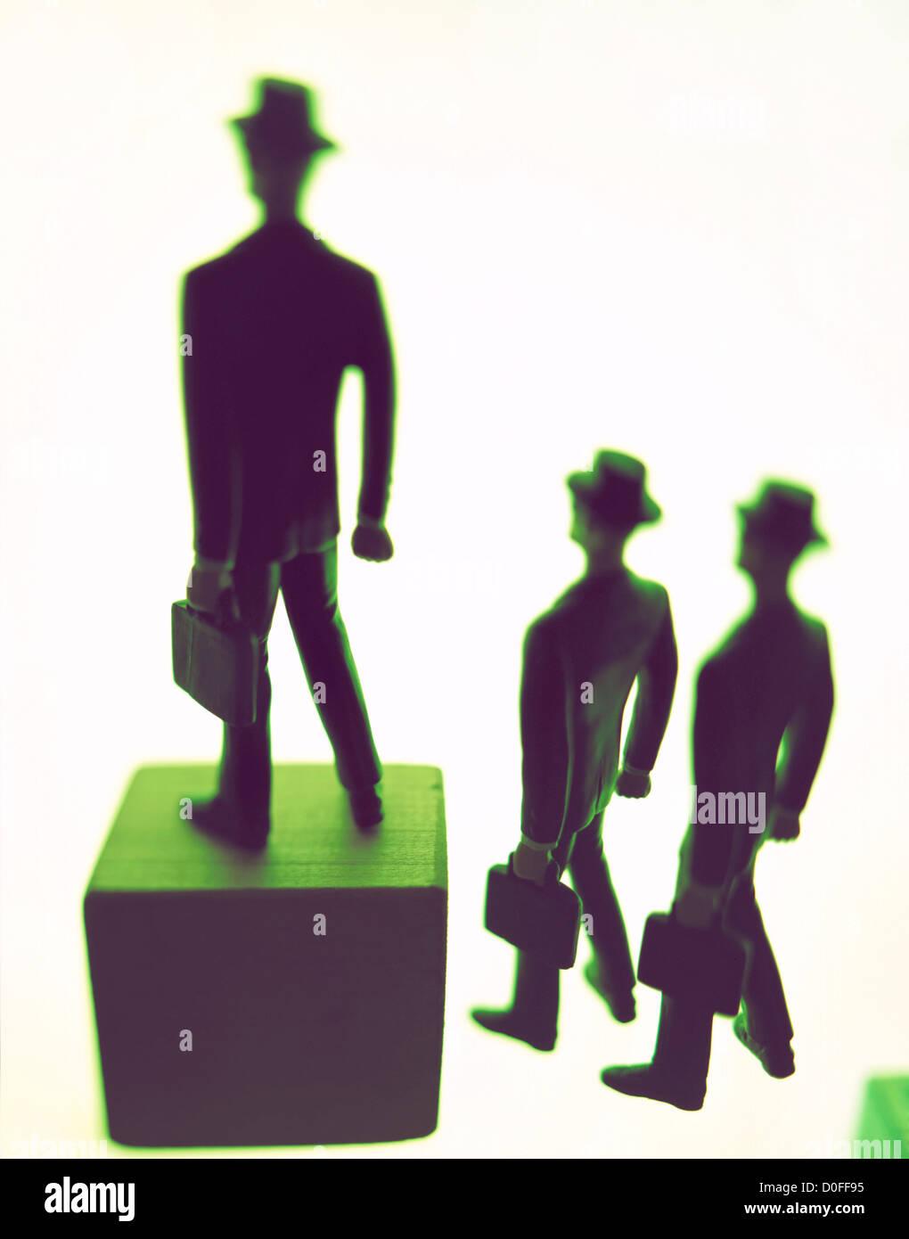 Empresario con maletín intensificando sobre un bloque por encima de 2 hombres en miniatura. ©mak Imagen De Stock
