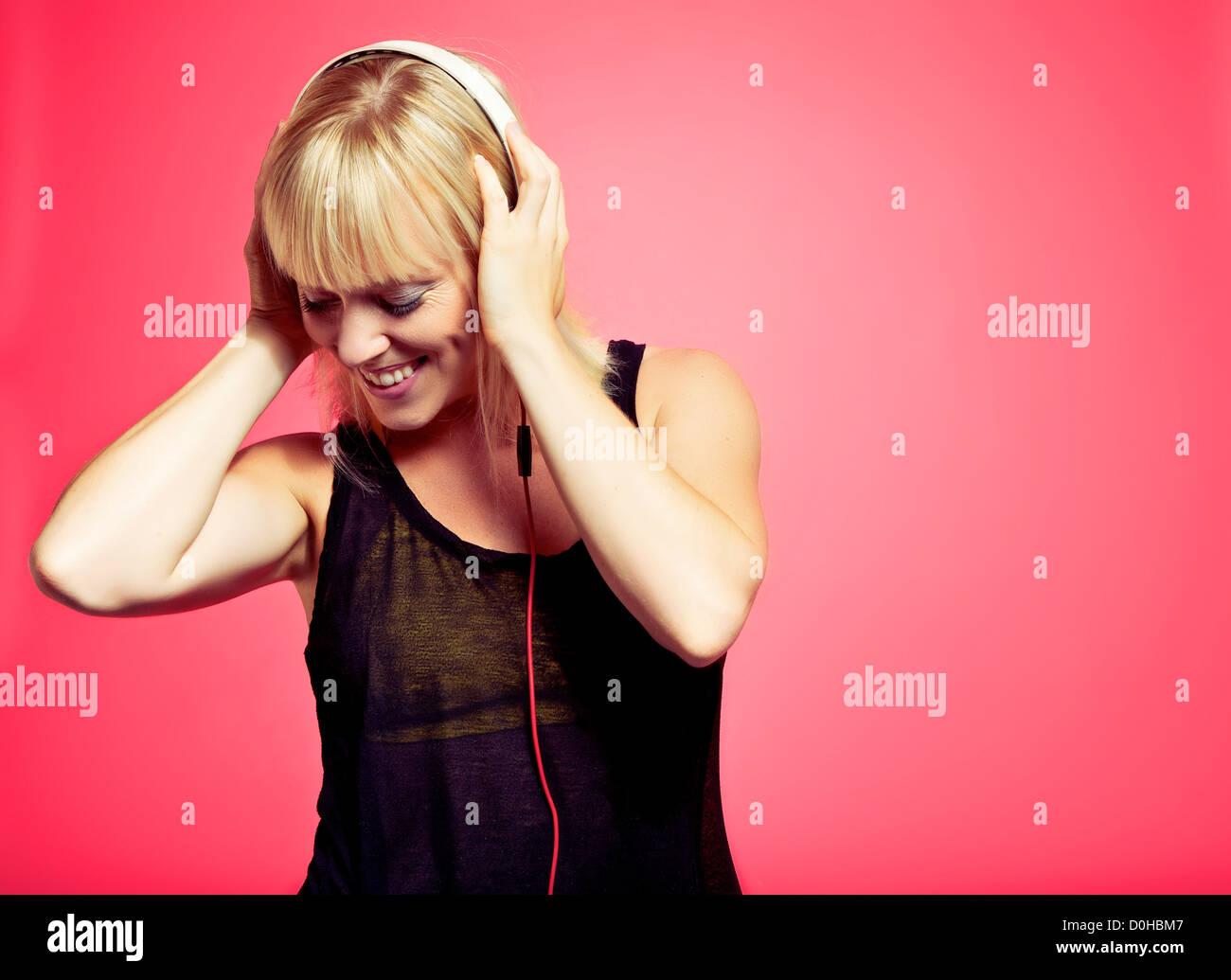 Atractiva mujer joven mirando hacia abajo mientras disfruta de la música desde su reproductor de mp3 Imagen De Stock