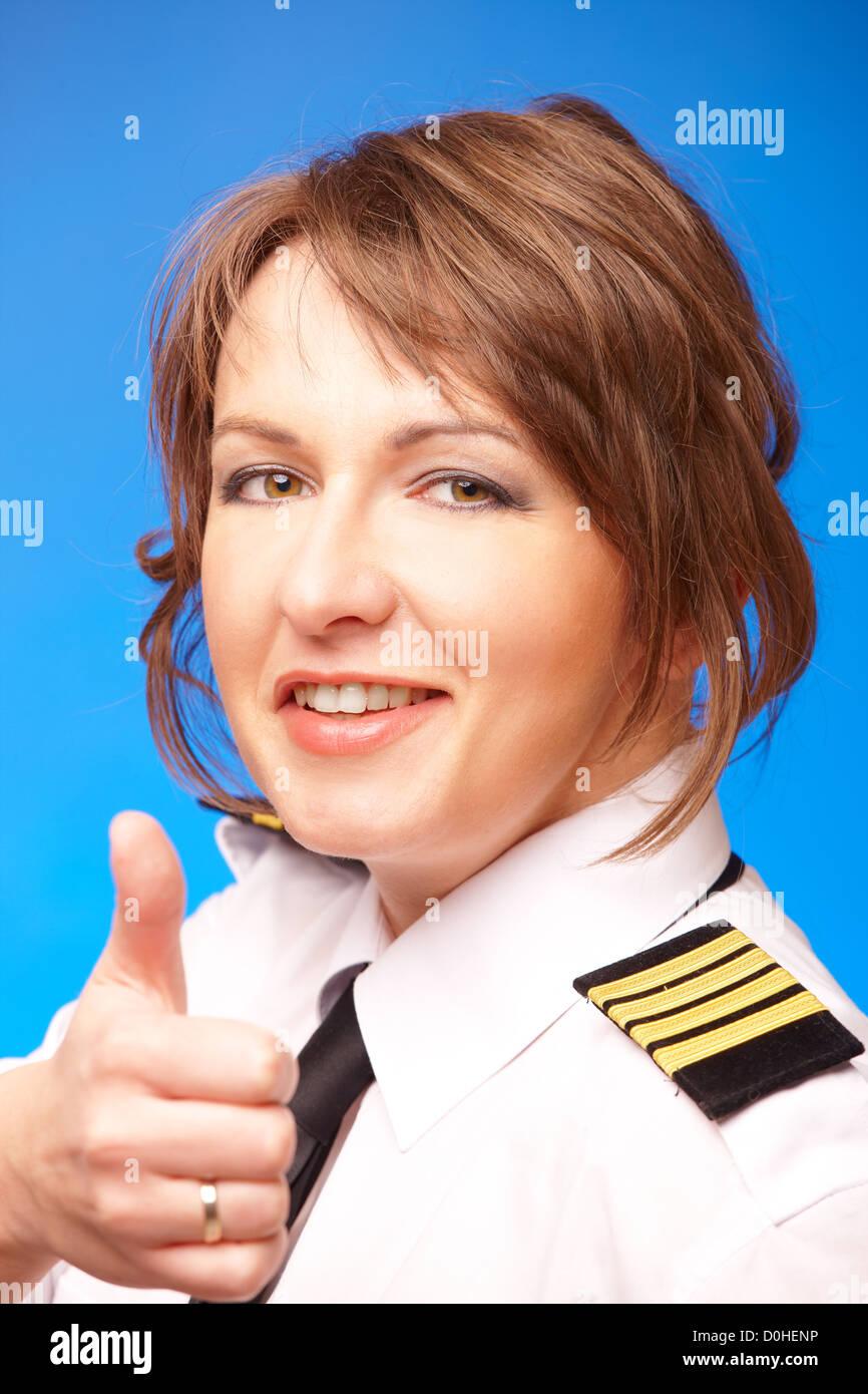 Hermosa piloto de línea aérea en uniforme con epauletes mostrando pulgar arriba gesto de aprobación, Imagen De Stock