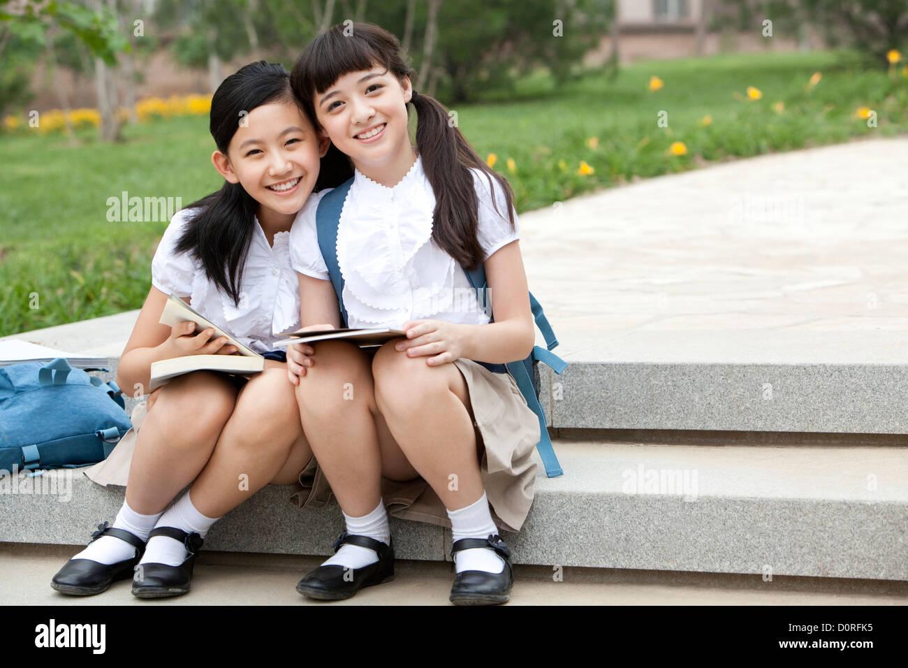 e26eabdce Las colegialas sentado en pasos con libros sonriendo felizmente ...