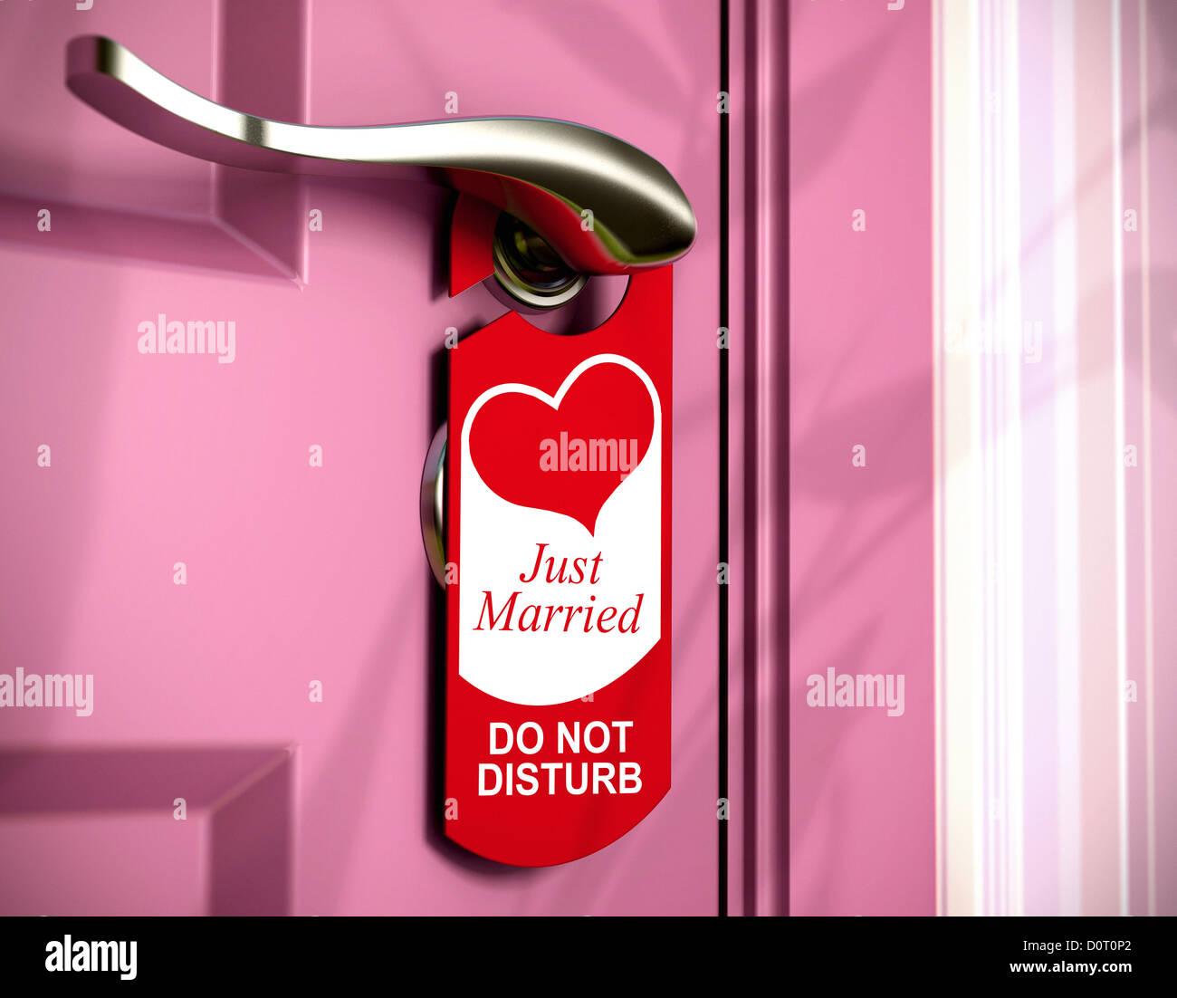 Recién casada escrito en un colgador de la puerta roja, ahorcado en un mango de metal de una puerta en la habitación Imagen De Stock
