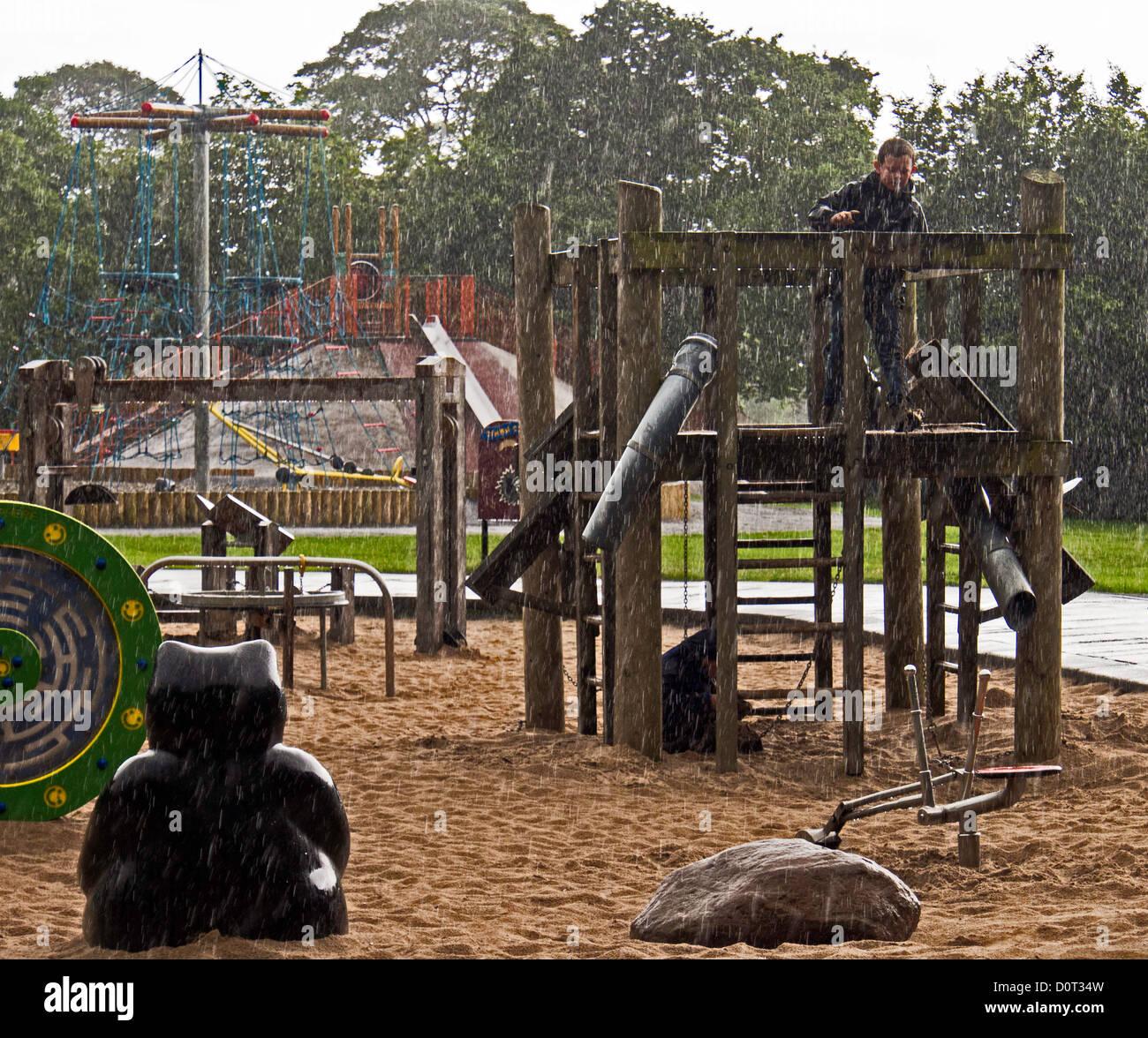Los niños disfrutan jugando bajo la lluvia torrencial con ropa de clima húmedo adecuado Imagen De Stock