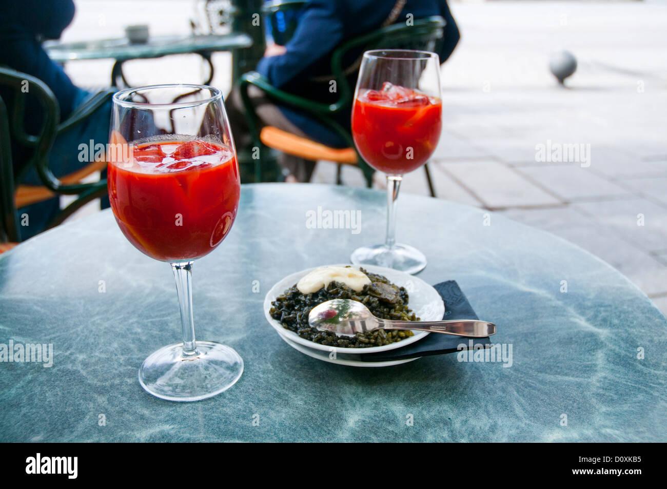 Dos vasos de zumo de tomate y de tapas españolas de arroz negro con alioli. Madrid, España. Imagen De Stock