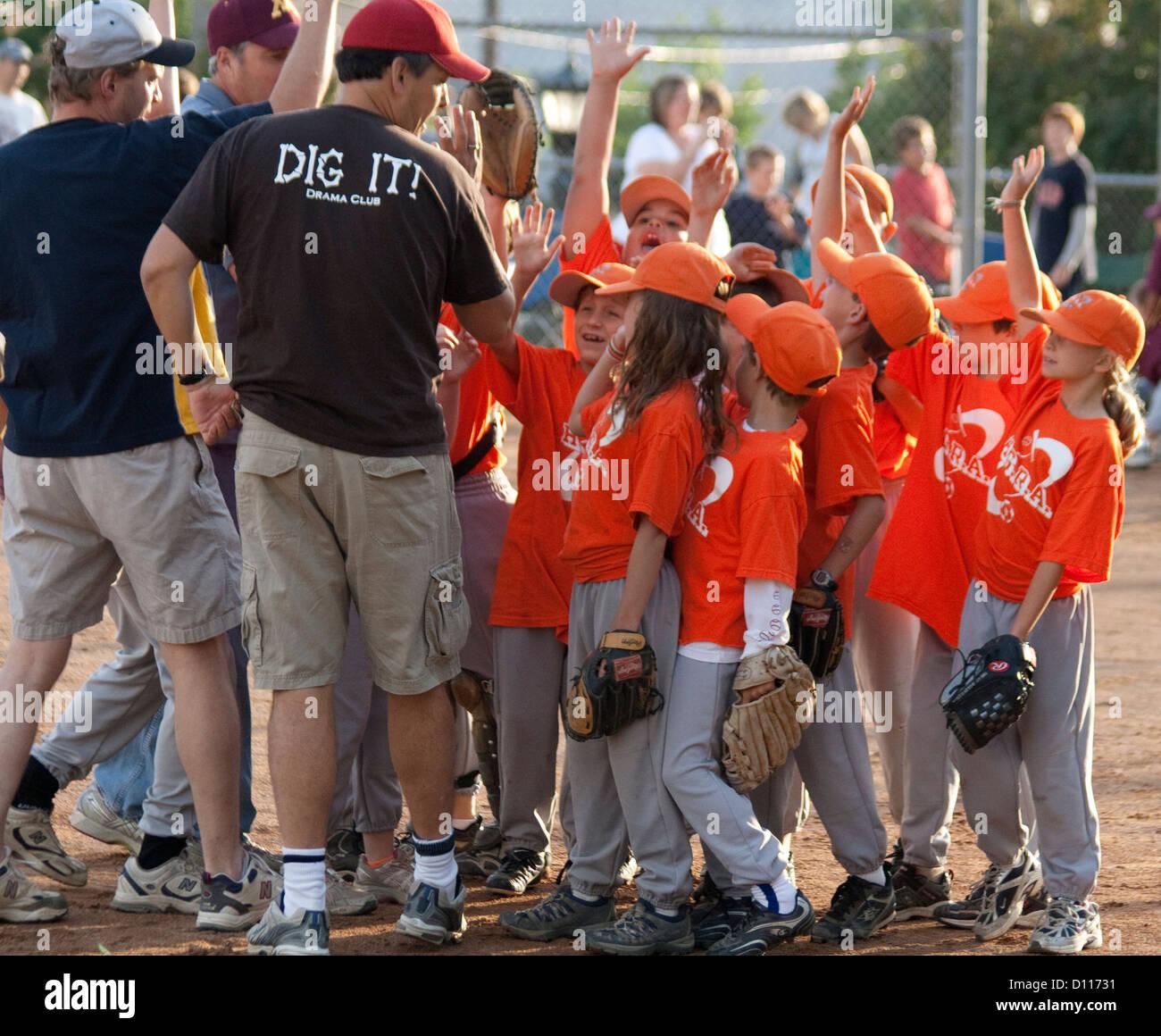 e5351c9e3b5a8 Niños y niñas mixto equipo de béisbol responder a entrenadores con manos  levantadas de 7 años