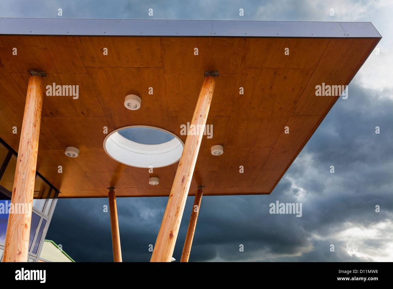 La arquitectura moderna marquesina con pilares de madera contra el cielo. Imagen De Stock