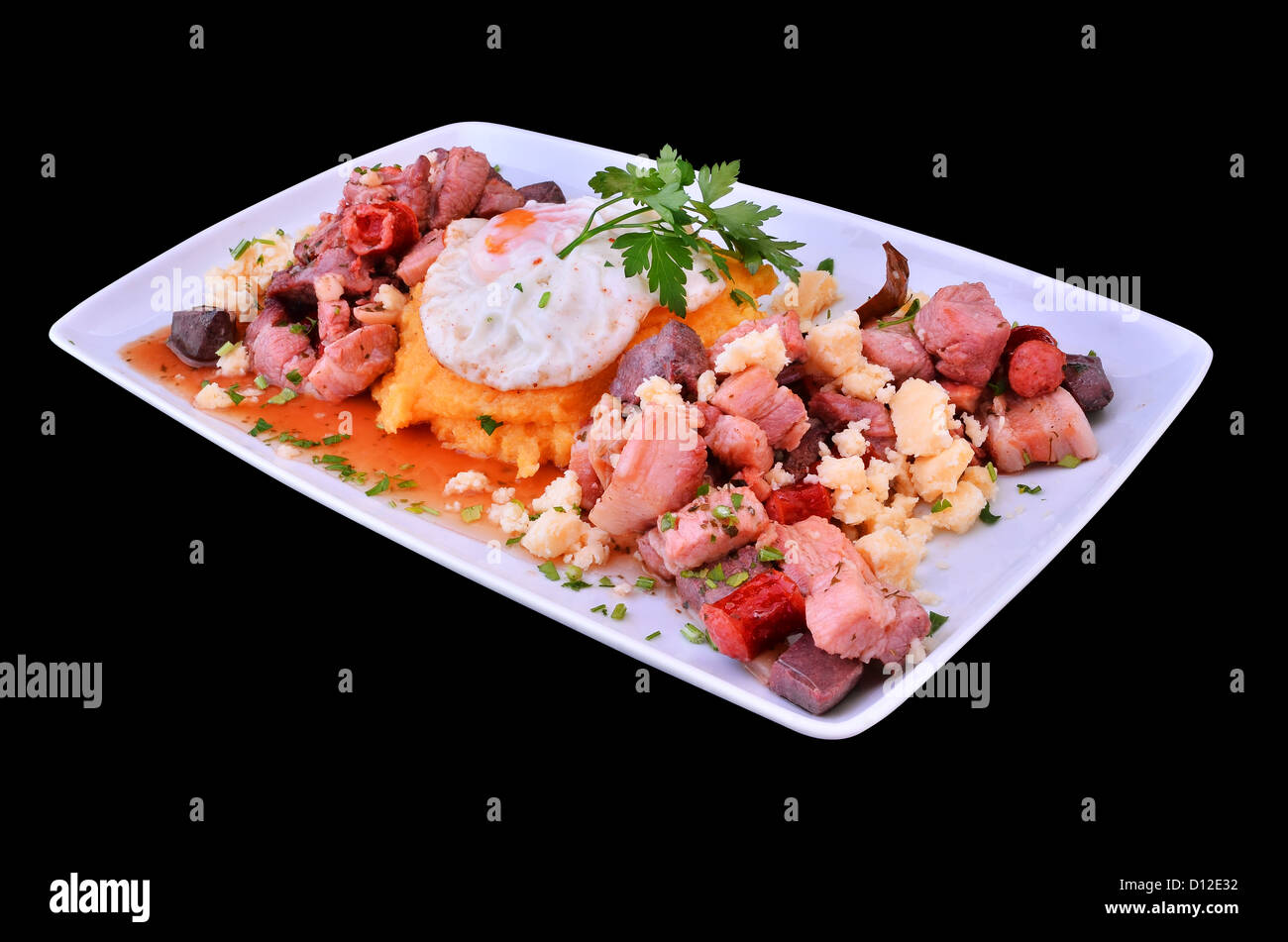 Trozos de carne de cerdo cocinada pan con ajo, queso tradicional, huevo frito y polenta (rumano: pomana porcului). Imagen De Stock