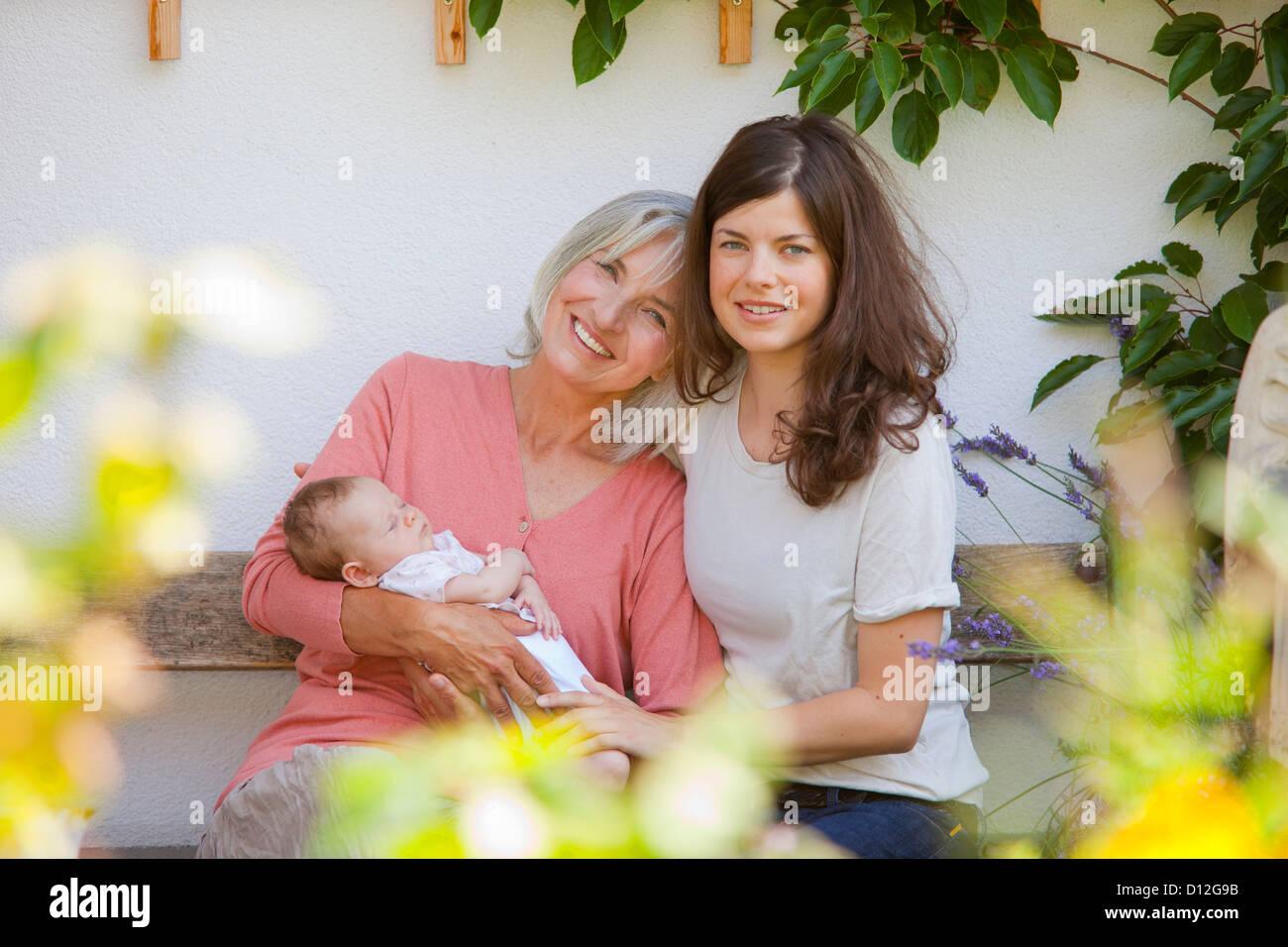 Alemania, Baviera, tres generaciones sentados juntos, sonriendo Imagen De Stock
