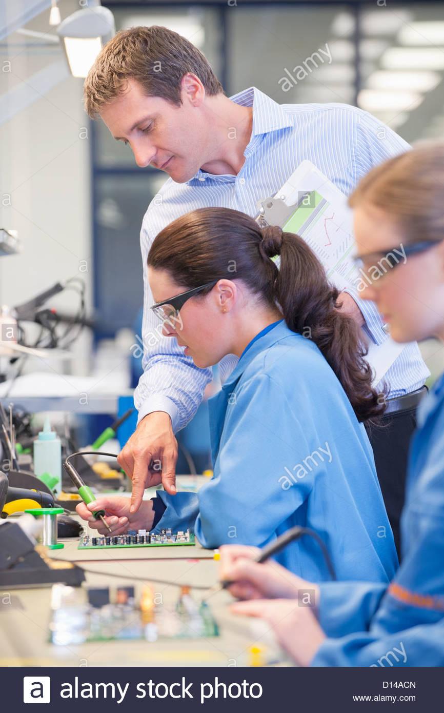 Supervisor Técnico de formación para soldar la placa de circuitos en línea de producción en Imagen De Stock