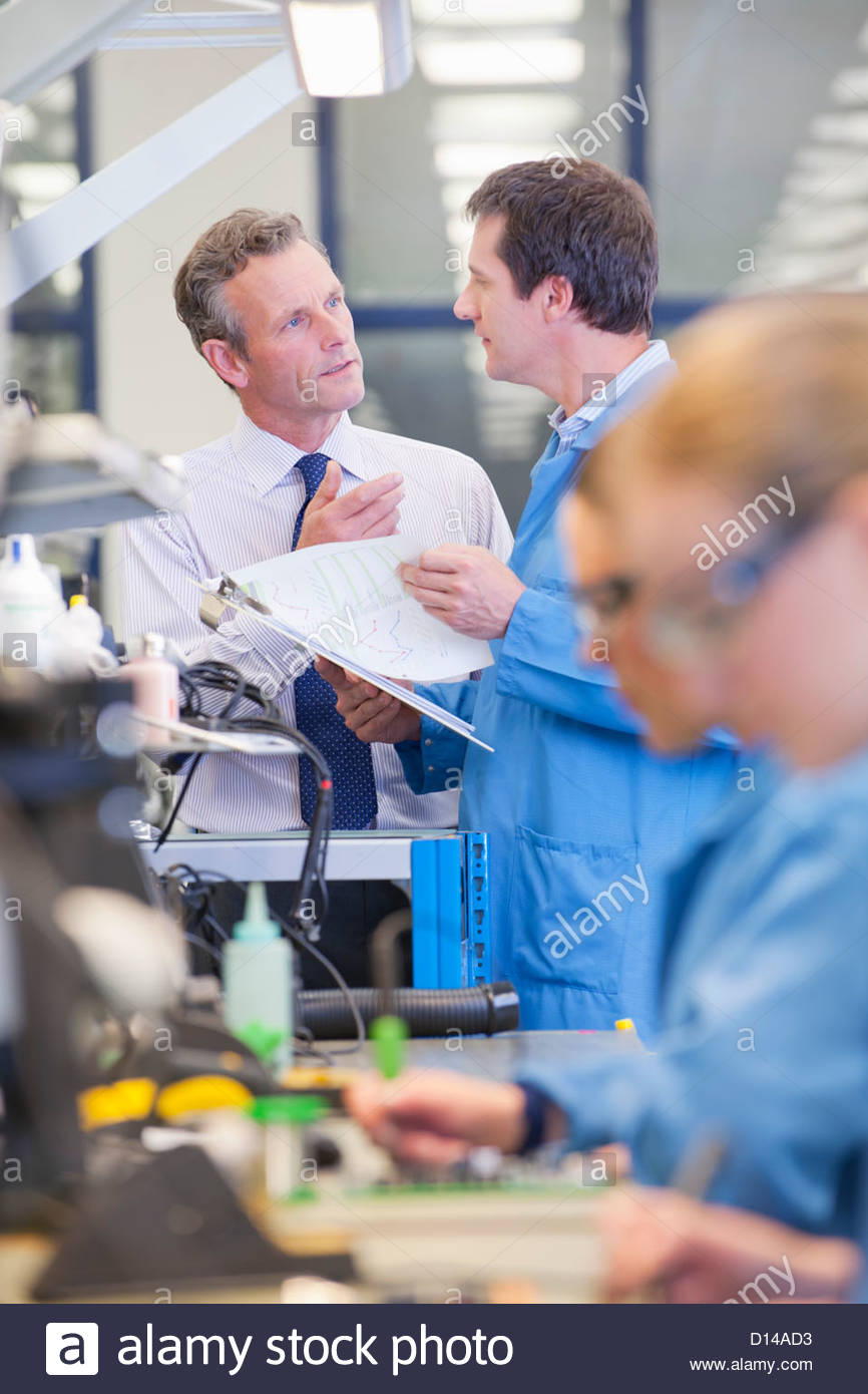 Empresario e ingeniero hablando a la línea de producción en la planta de fabricación de circuito Imagen De Stock