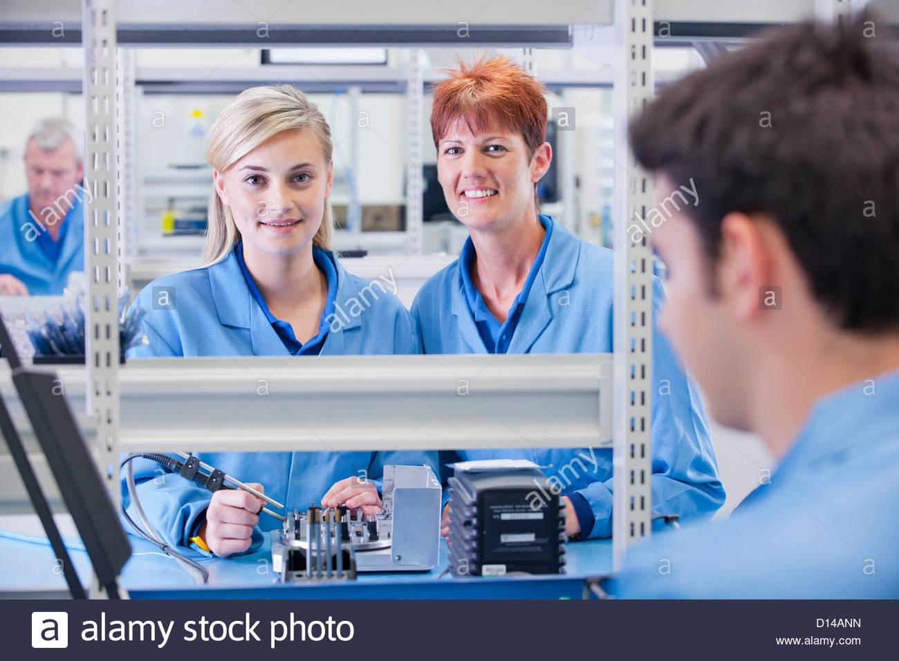 Retrato de sonriente supervisor técnico y montaje de circuito impreso en la planta de fabricación Imagen De Stock