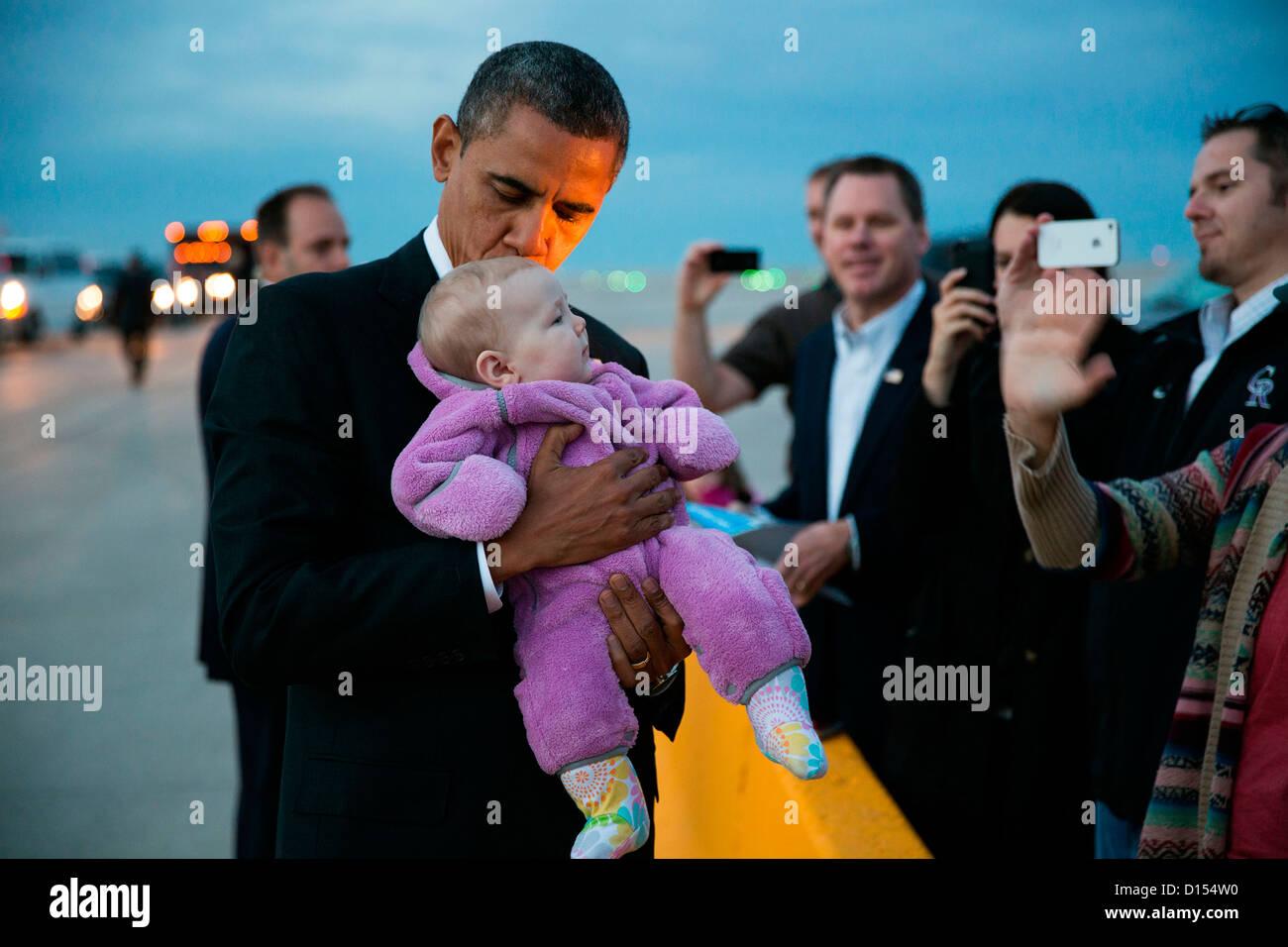 El presidente estadounidense, Barack Obama, besa a un bebé en el asfalto tras su llegada en una campaña Imagen De Stock