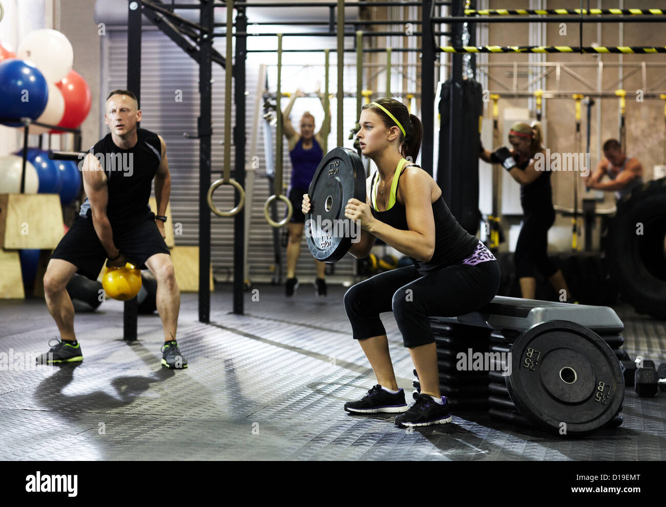 La gente de entrenamiento de circuito en el gimnasio Imagen De Stock