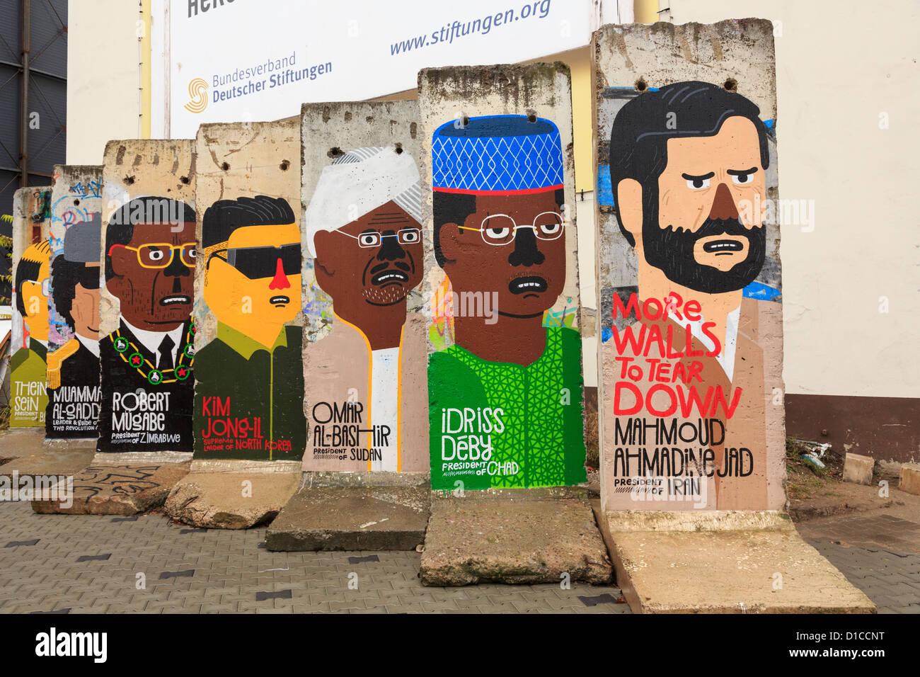 Escena callejera con el resto de secciones del muro pintado con murales que muestran un retrato de dictadores del Imagen De Stock