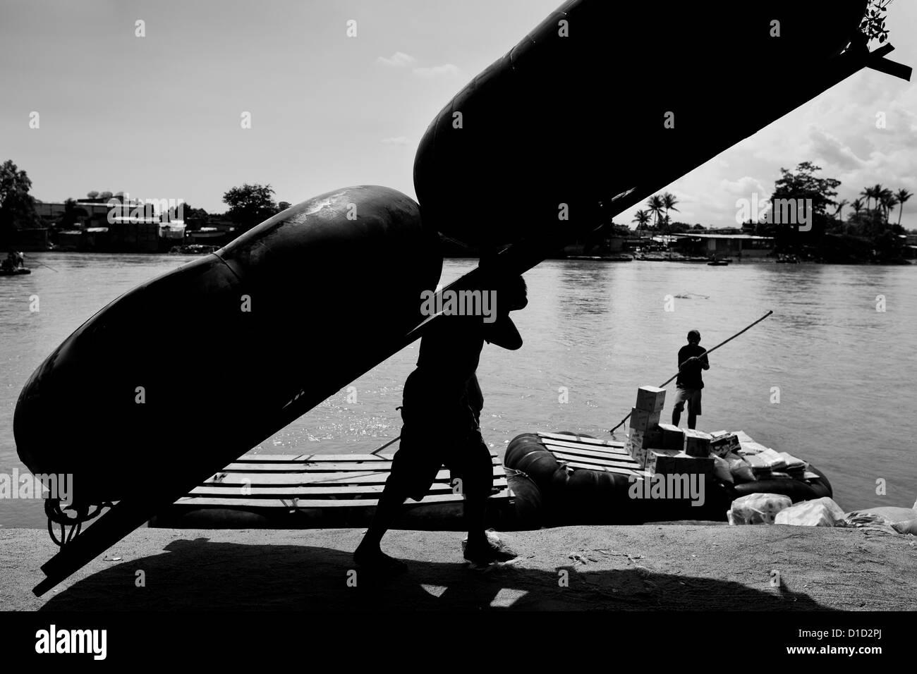 Un guatemalteco barquero lleva un tubo interior de la improvisada balsa en la orilla del río suchiate, en Tecún Imagen De Stock