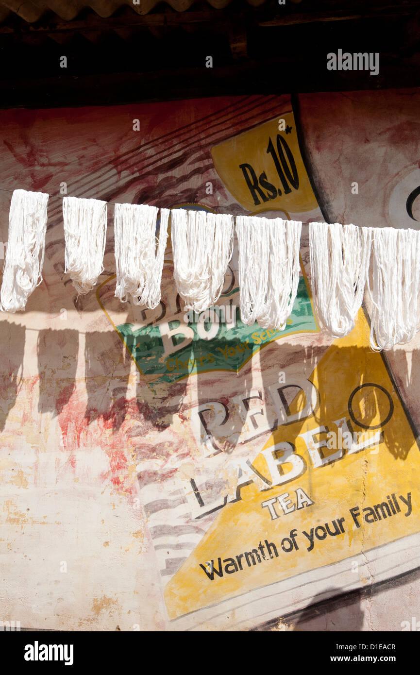 Las madejas de lavado hilar seda cruda para colgar en seco, con pintadas de anuncio, Naupatana village, Orissa, Imagen De Stock