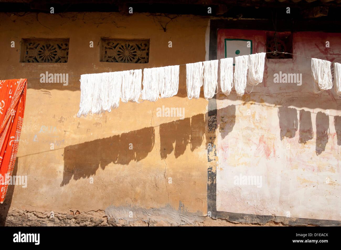 Las madejas de lavado hilar seda cruda colgando para secar a lo largo de una pared de la casa de aldea, la aldea Imagen De Stock