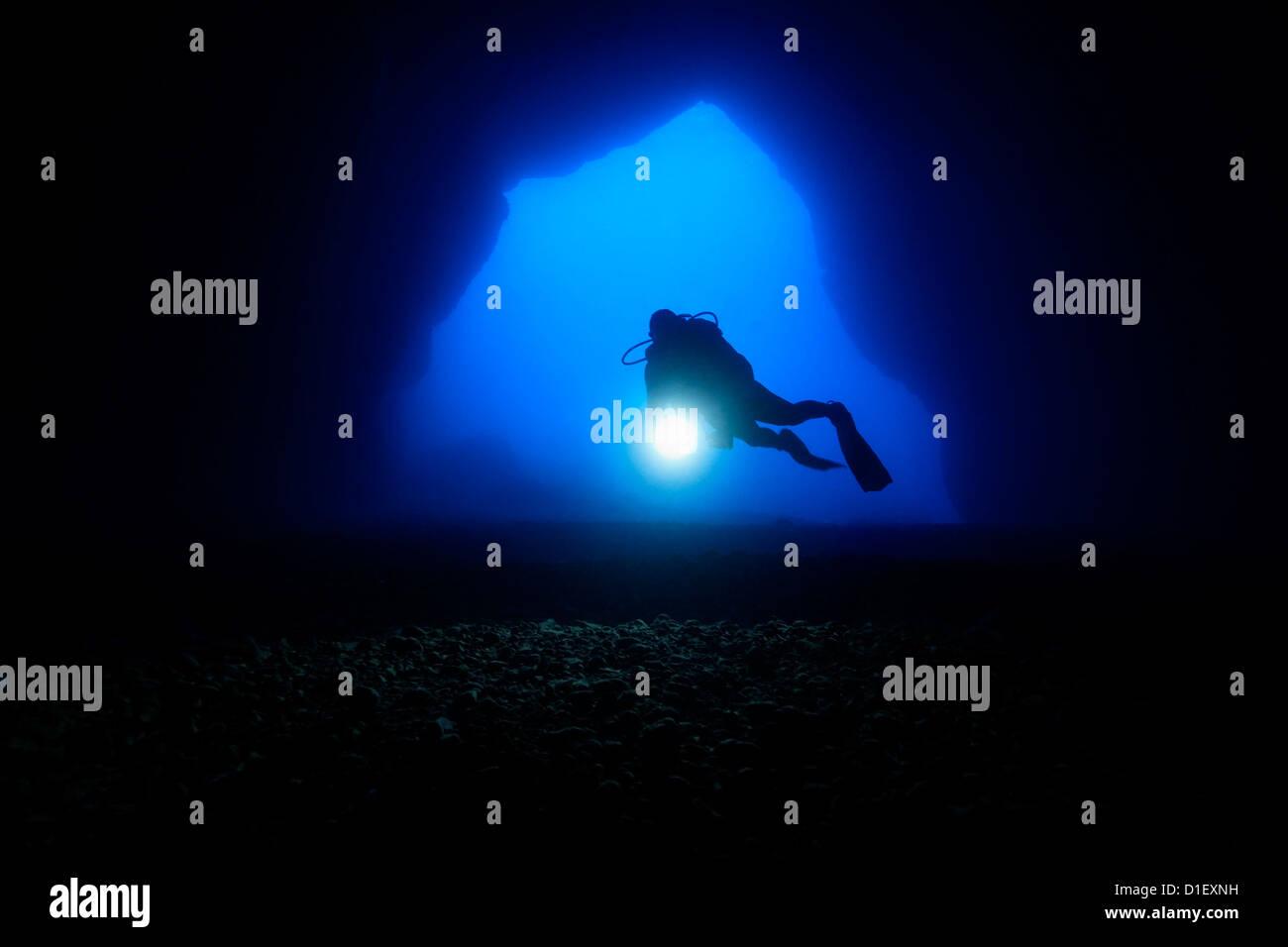 Diver en la entrada de una cueva, cerca del mar Mediterráneo, Malta, Gozo filmación subacuática Foto de stock