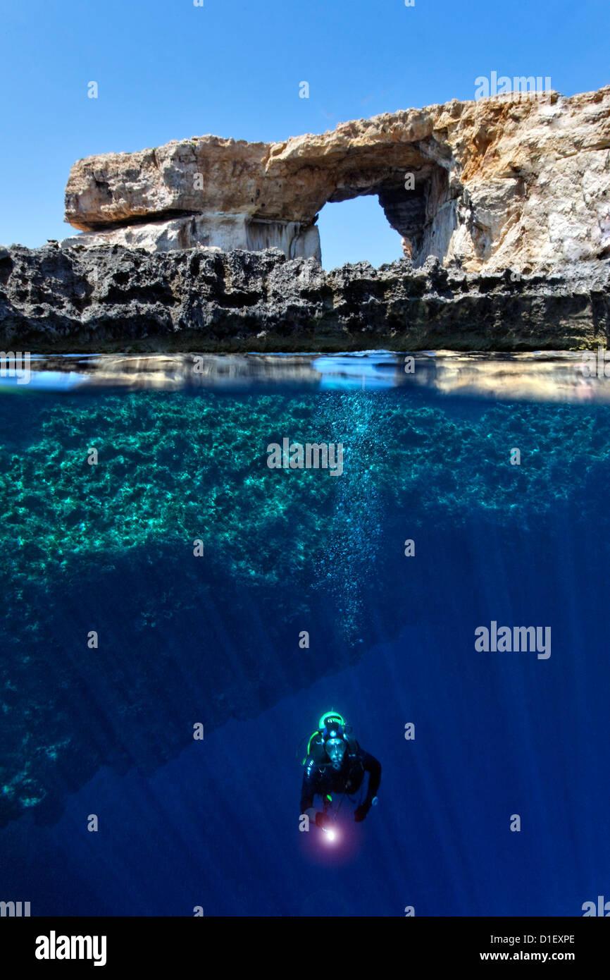 Split shot mitad y mitad con diver y arco de roca ventana azul en el Mar Mediterráneo cerca de Gozo, Malta Foto de stock