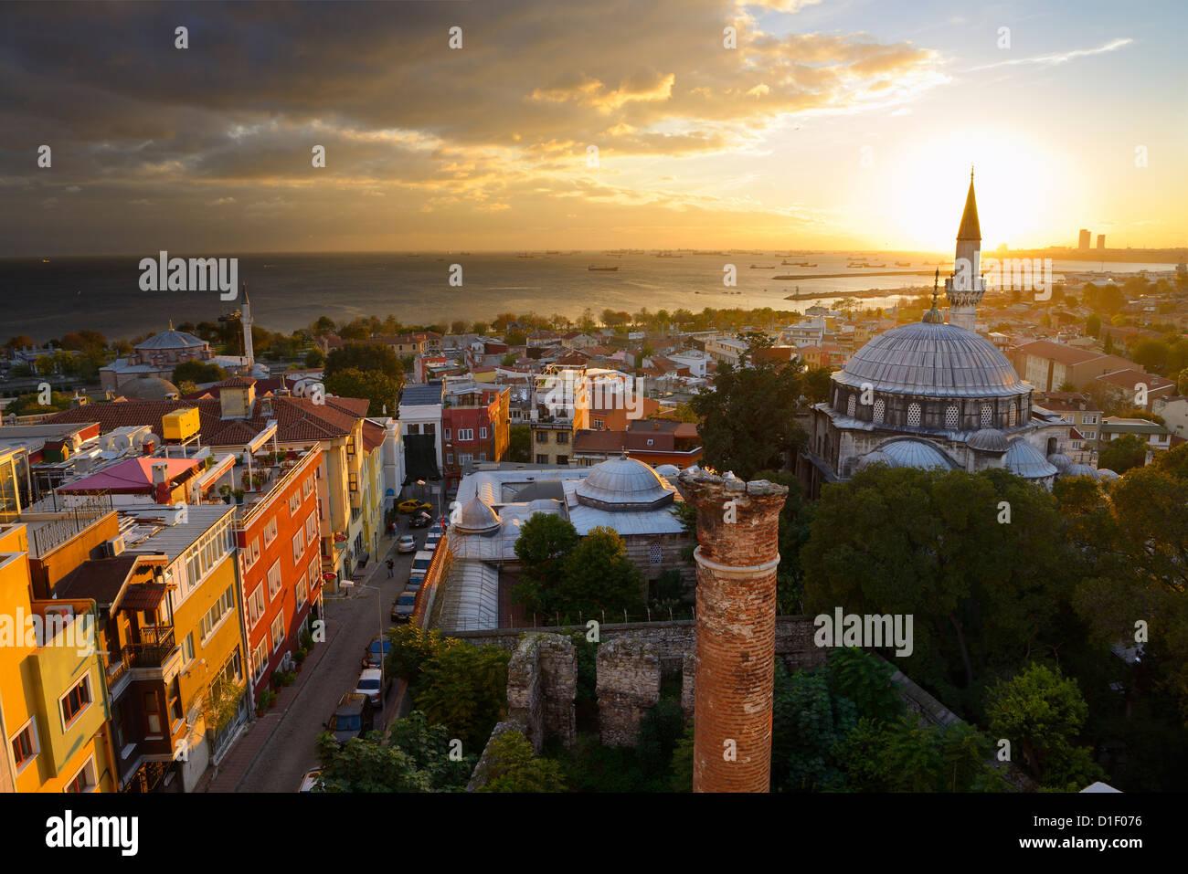 Puesta del sol detrás del minarete de la mezquita de Sokollu Mehmet Pasha con brillo dorado sobre las casas Imagen De Stock